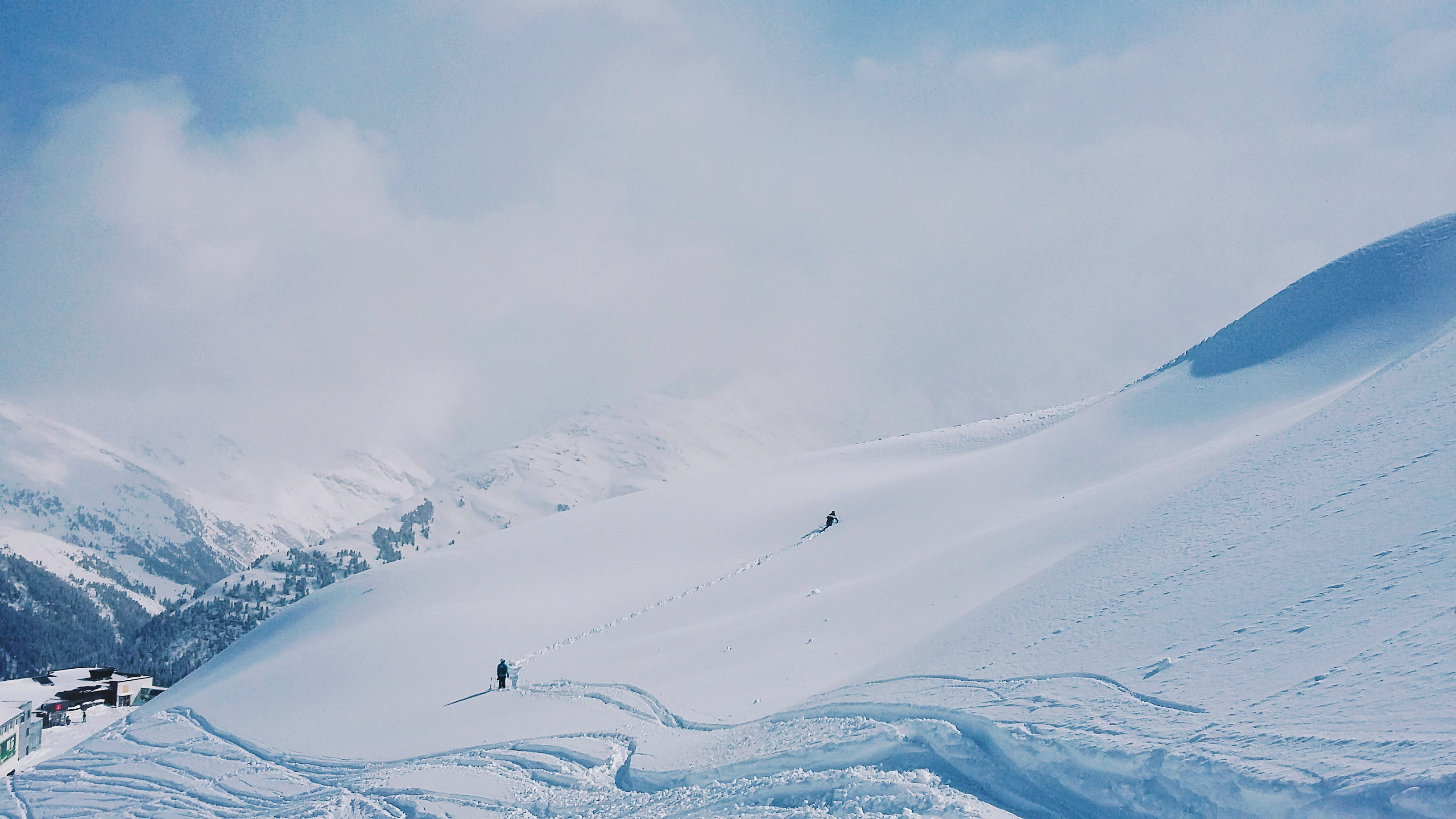 two people hiking on snow covered hill during day