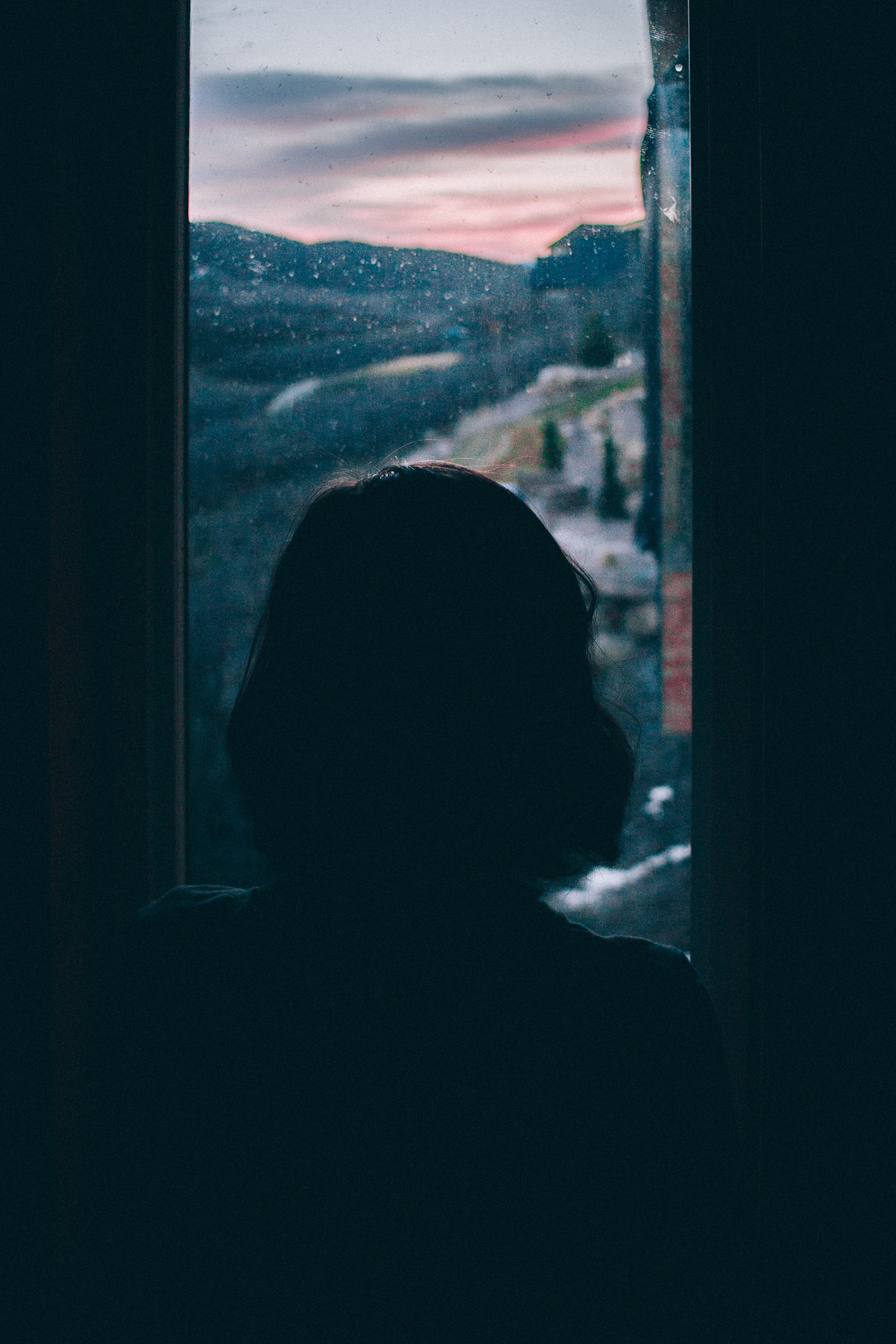women's silhouette facing outside window