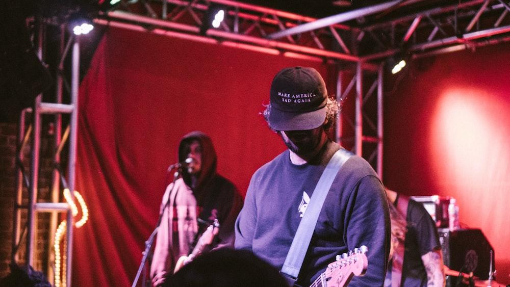 man playing guitar near man singing at stage