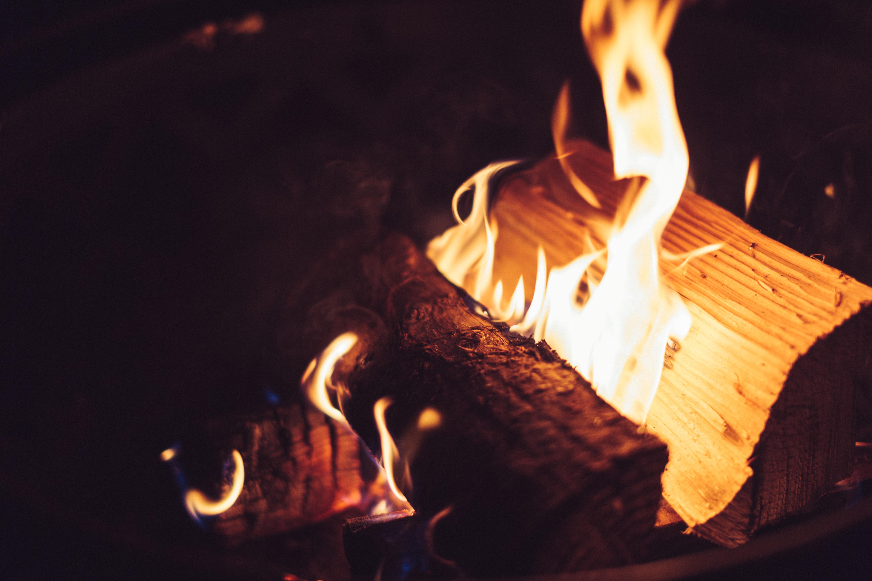 Logs of wood burn in an outdoor firepit
