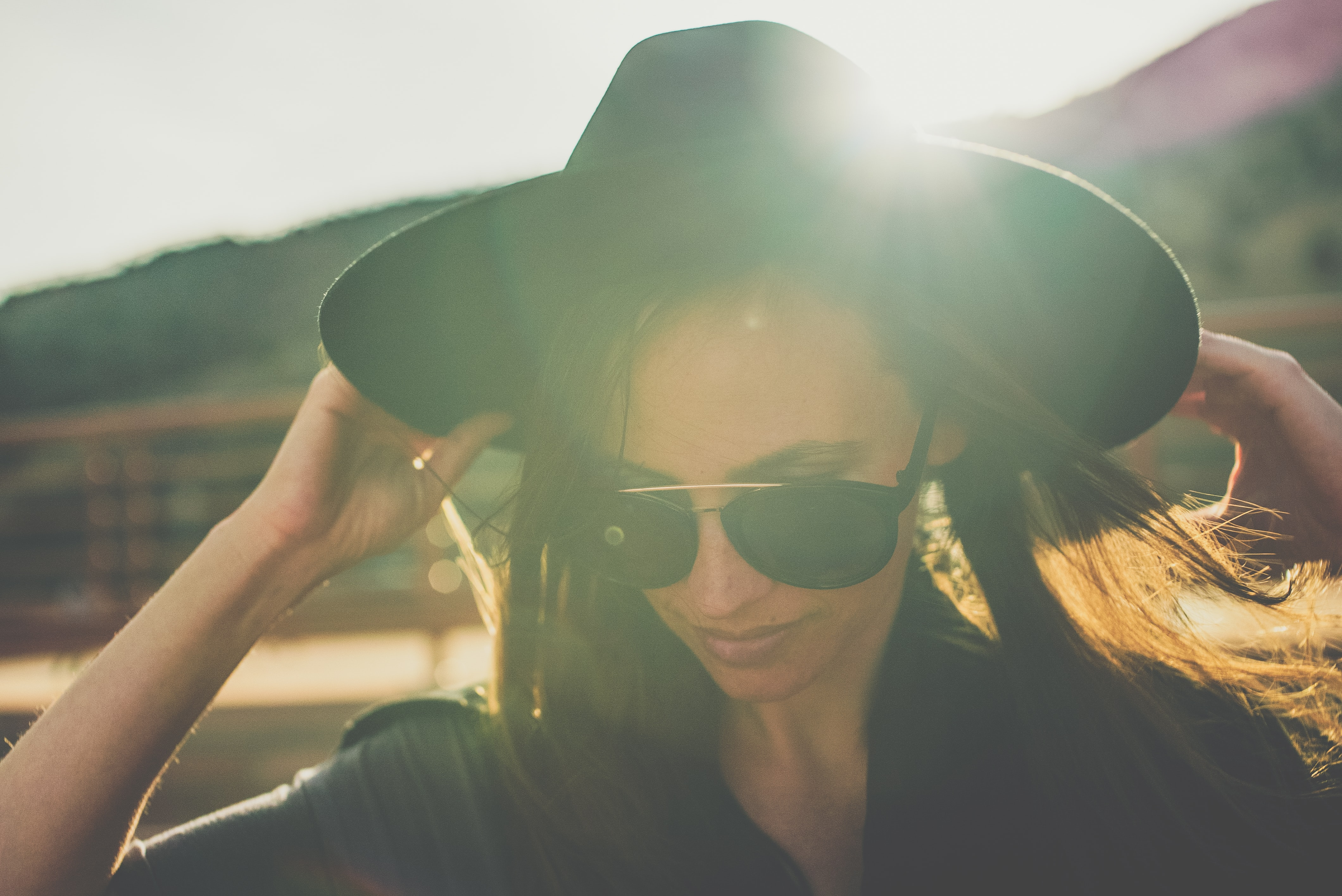 A woman in sunglasses holds the brim of her black hat, with sunlight shining behind her
