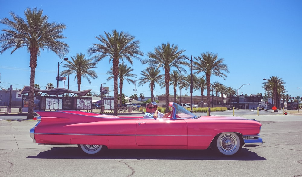 people in pink convertible coupe