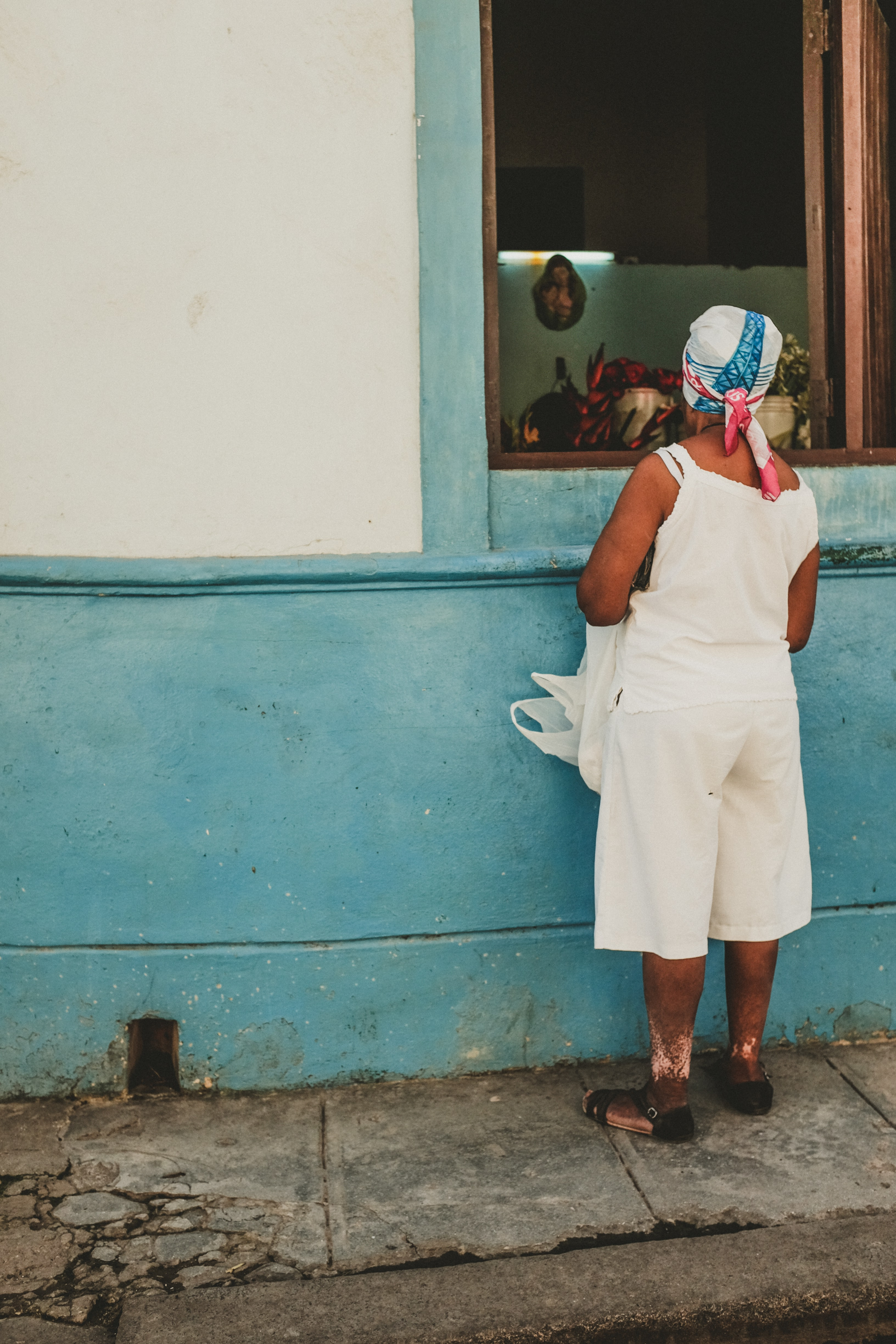 An old woman wearing white, standing in front of a blue and white wall on the walking path in old Havana.