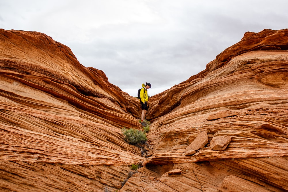 person in between rock formation during daytime