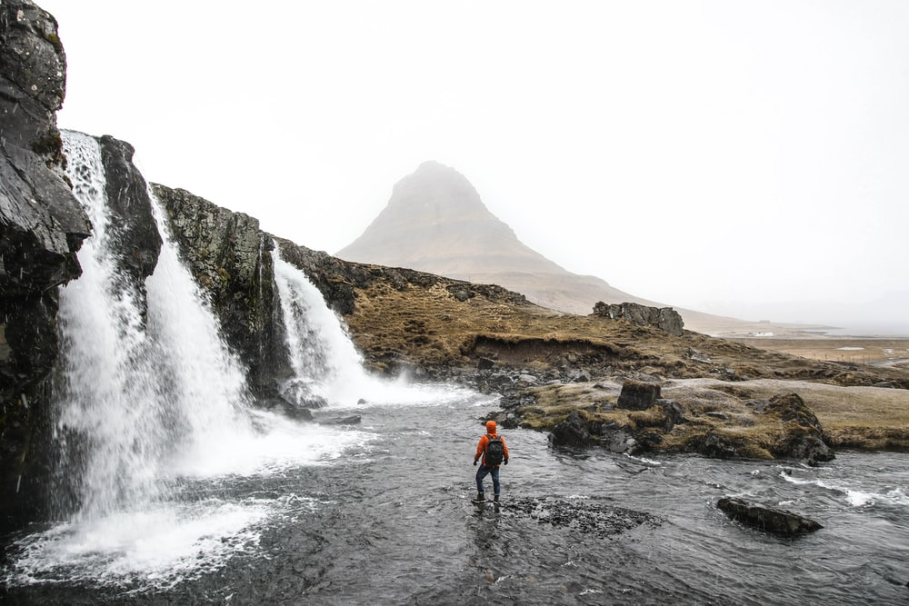 man with backpack standing on river beside waterfalls