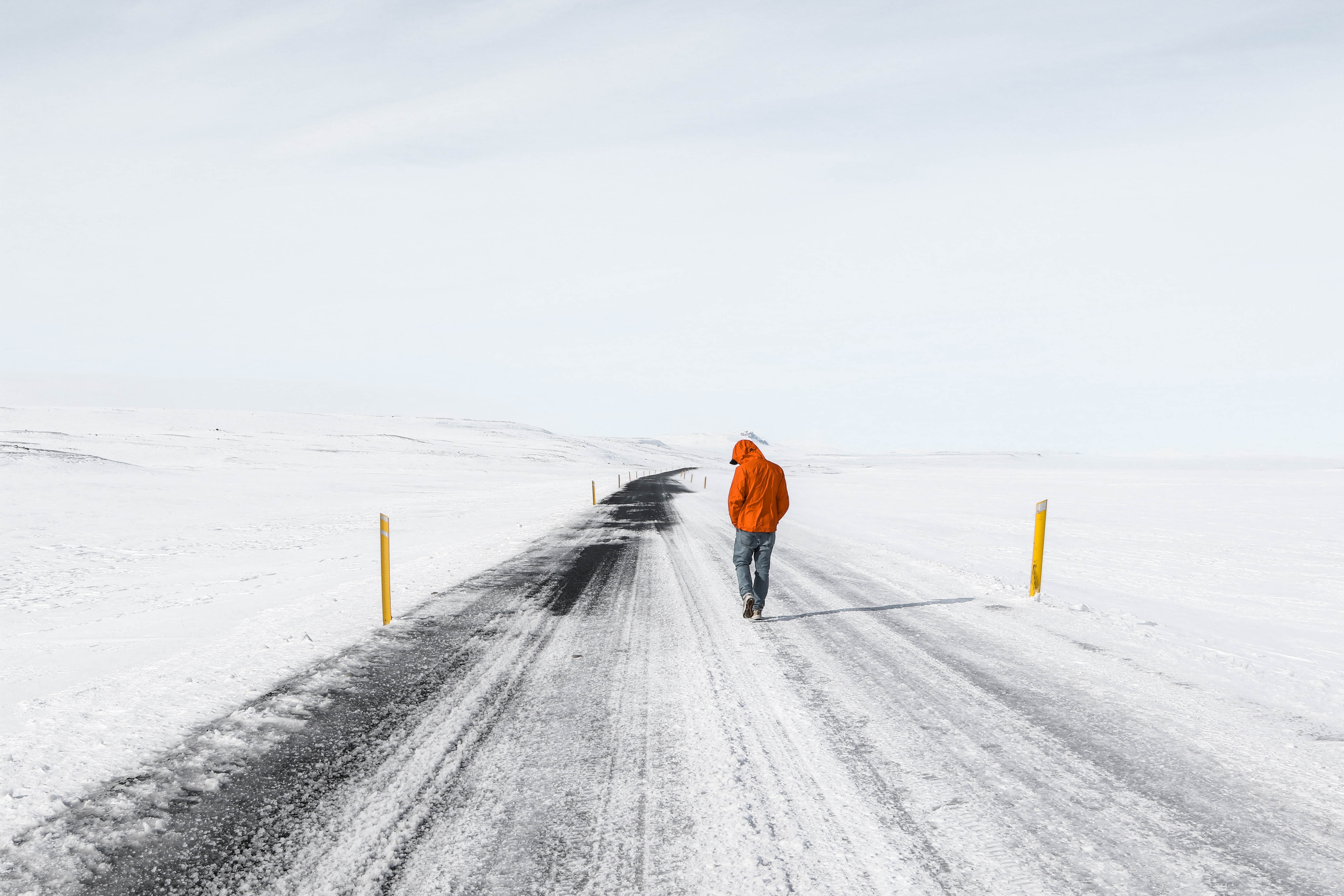 A lone man walking on a snowy road surrounded by snow-covered fields