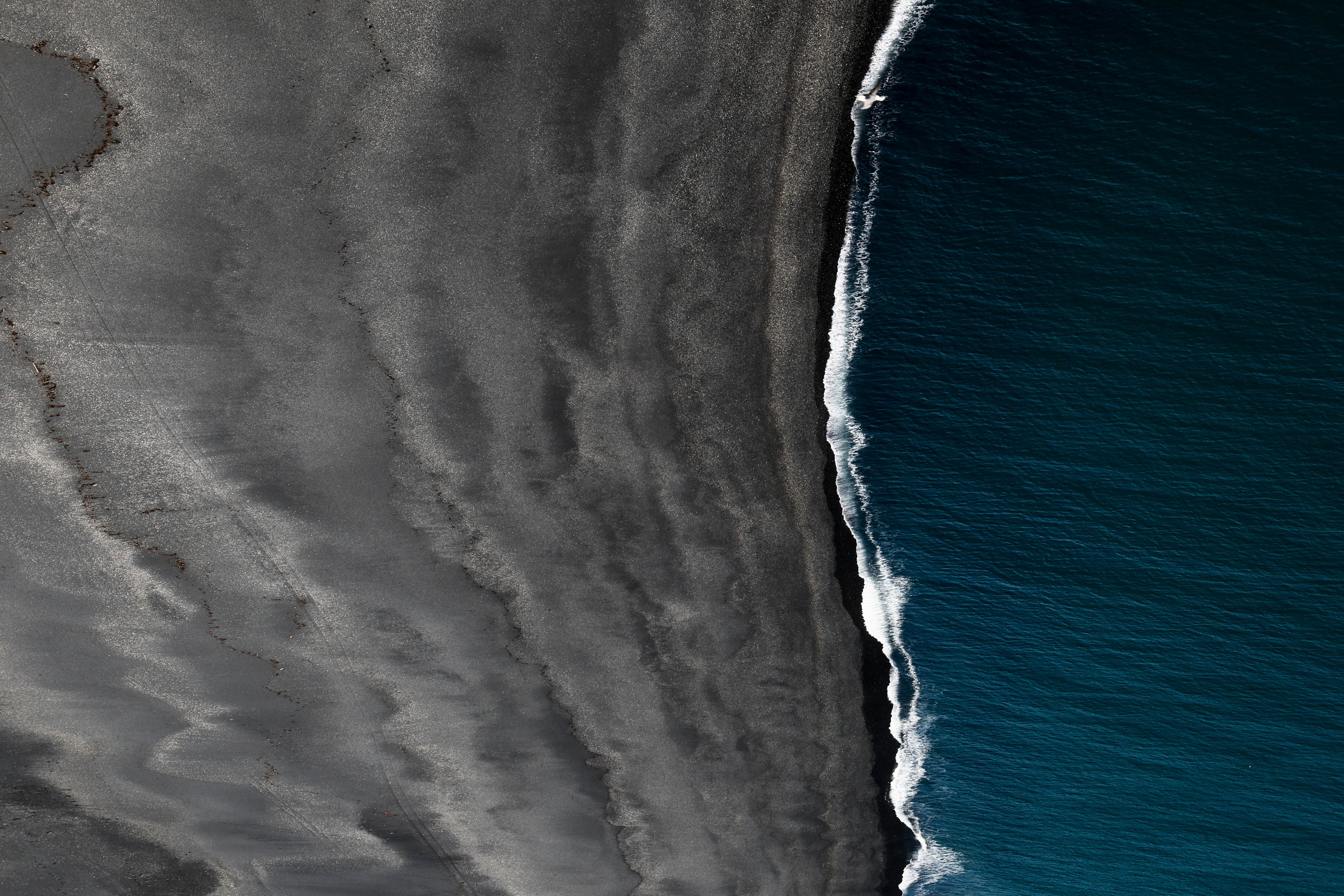 Drone aerial view of the ocean washing on the black sand beach in Vik