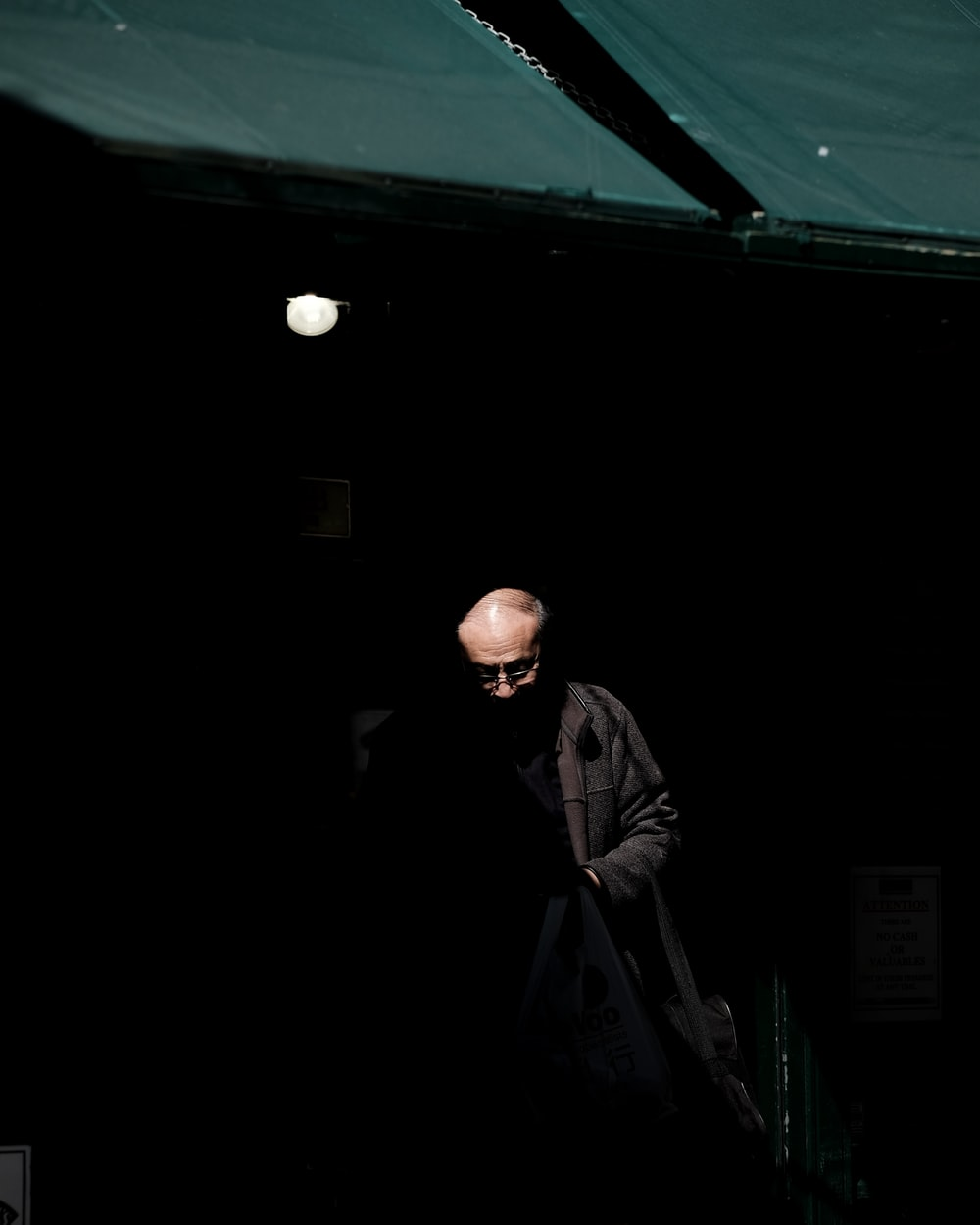 man wearing black jacket inside dark room