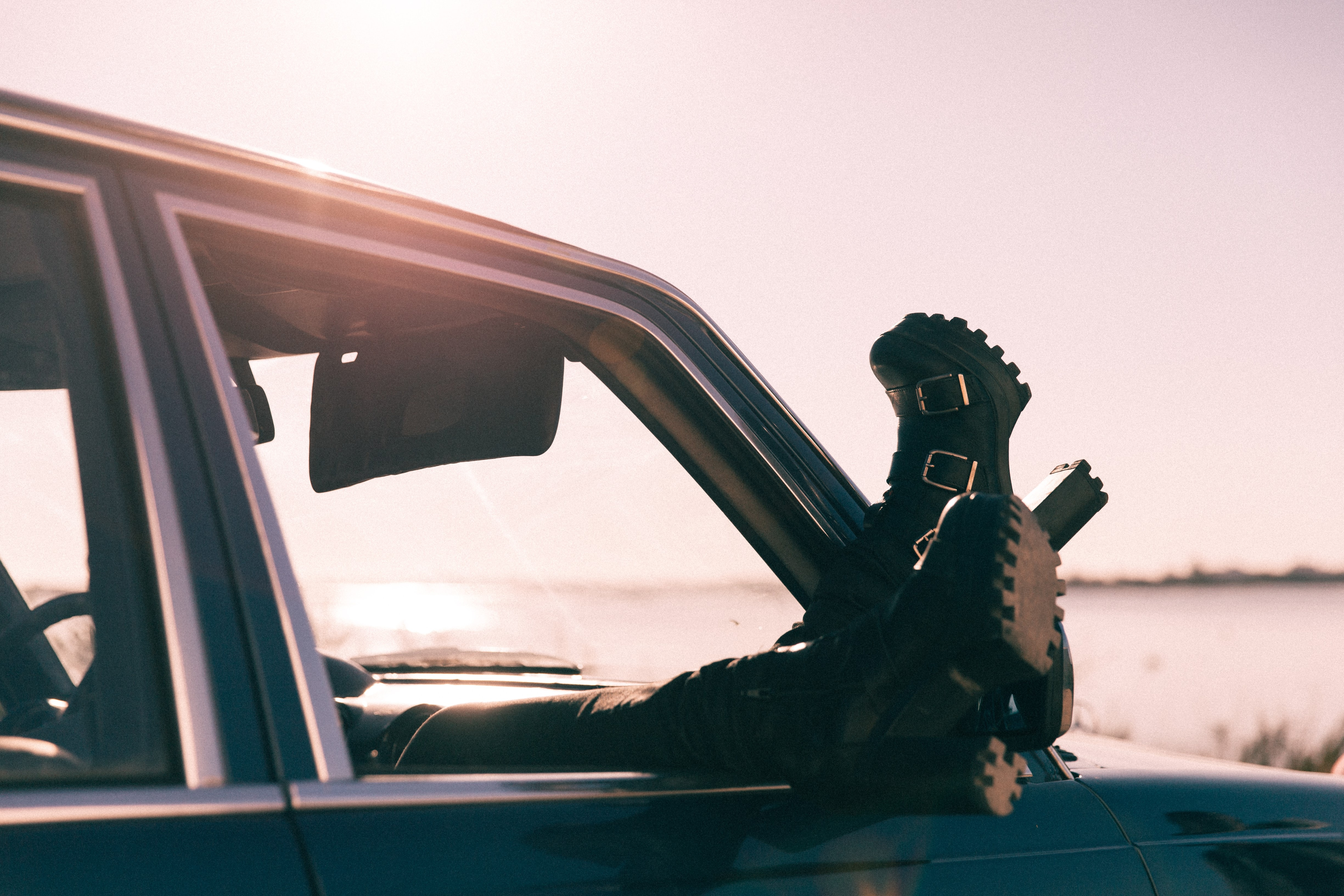 Person rests boots out of a car window in the sunshine
