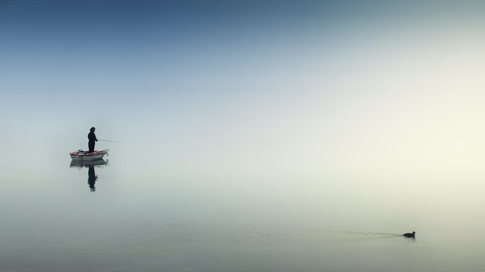 rule of thirds photography of man on boat