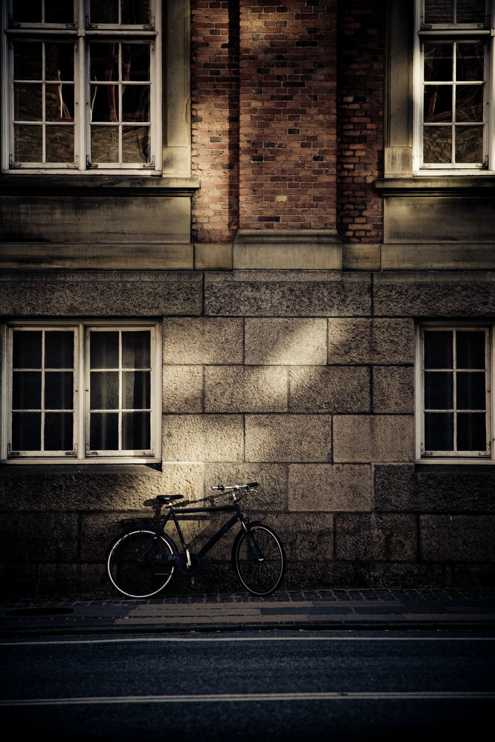 black mountain bicycle in front of brown concrete house
