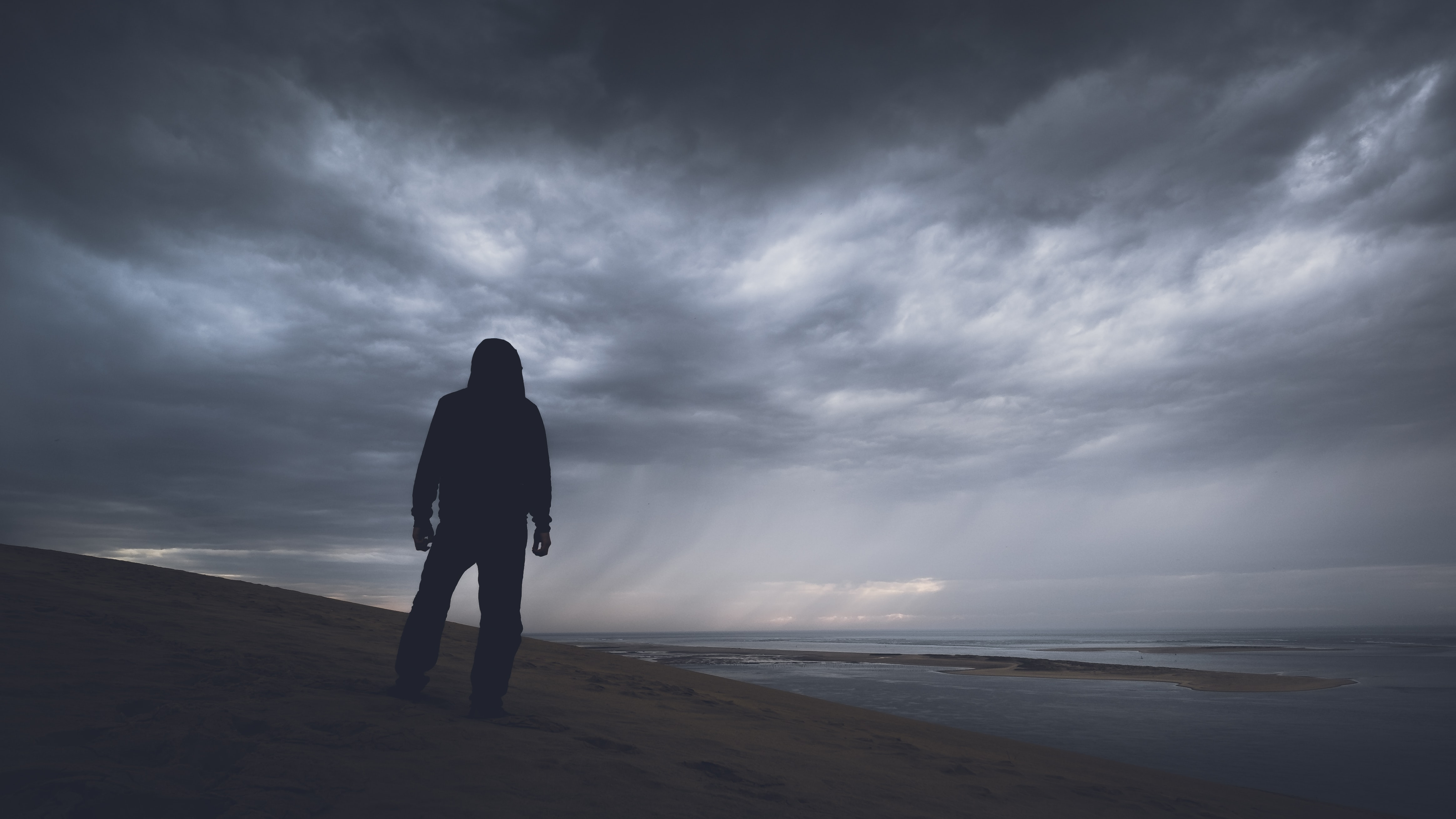 silhouette photography of person under gray clouds