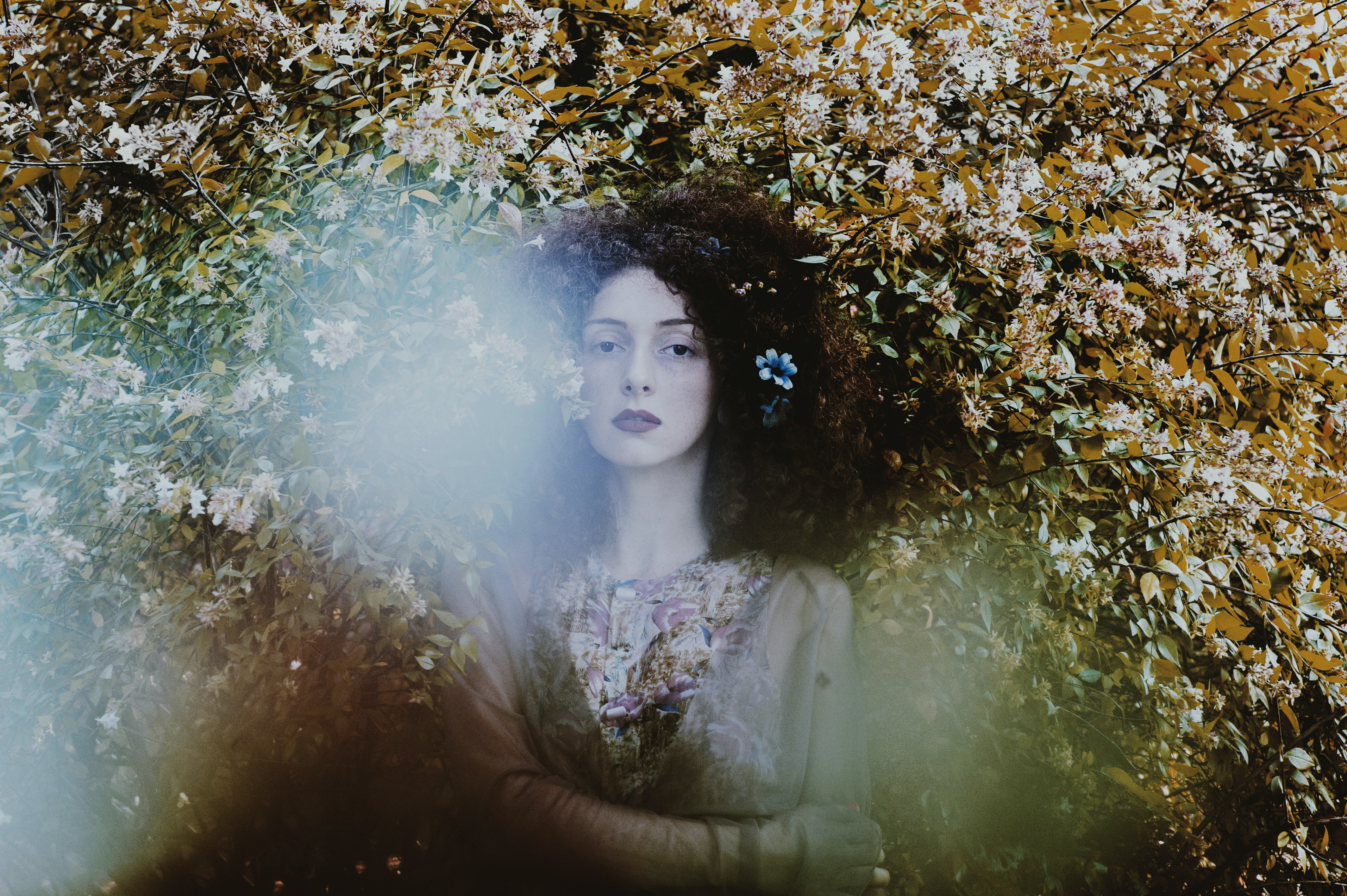 A curly-haired woman with a flower in her hair stands in leafy foliage, looking outward