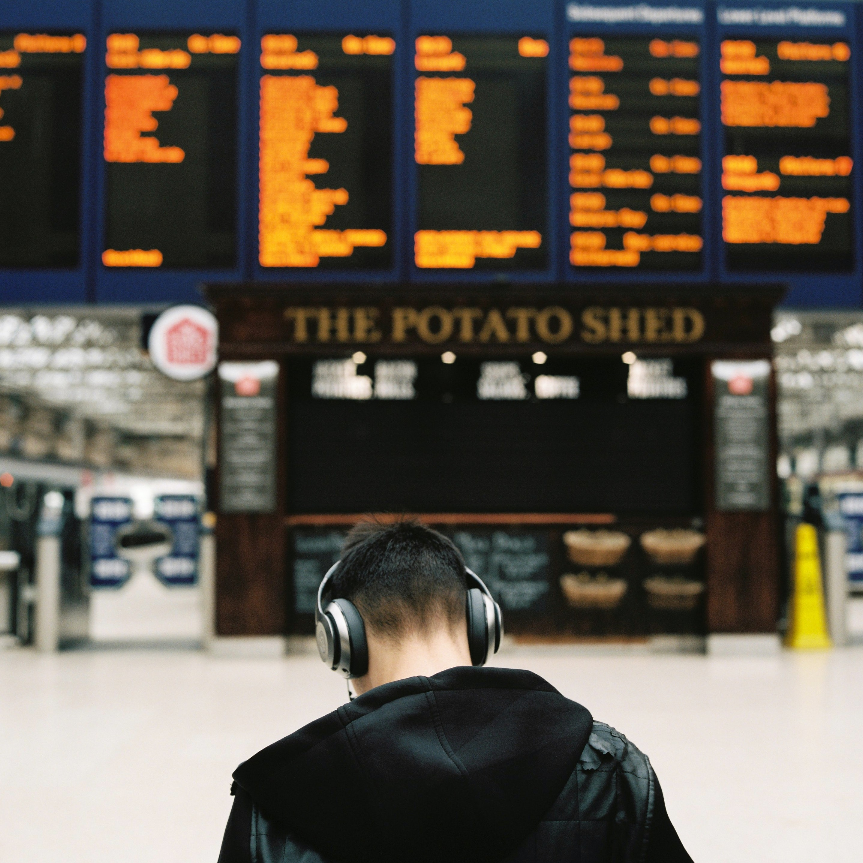 Back of a person with headphones in the Glasgow train station near the arrivals/departures board