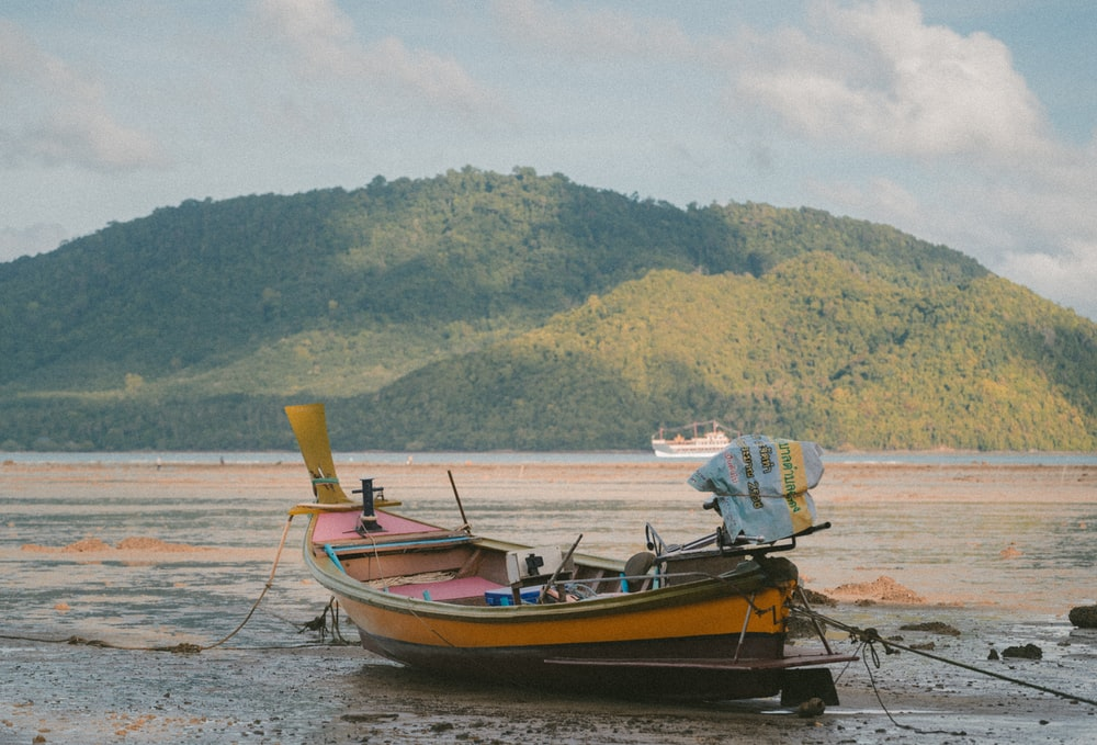 orange boat on seashore during daytime across mountain