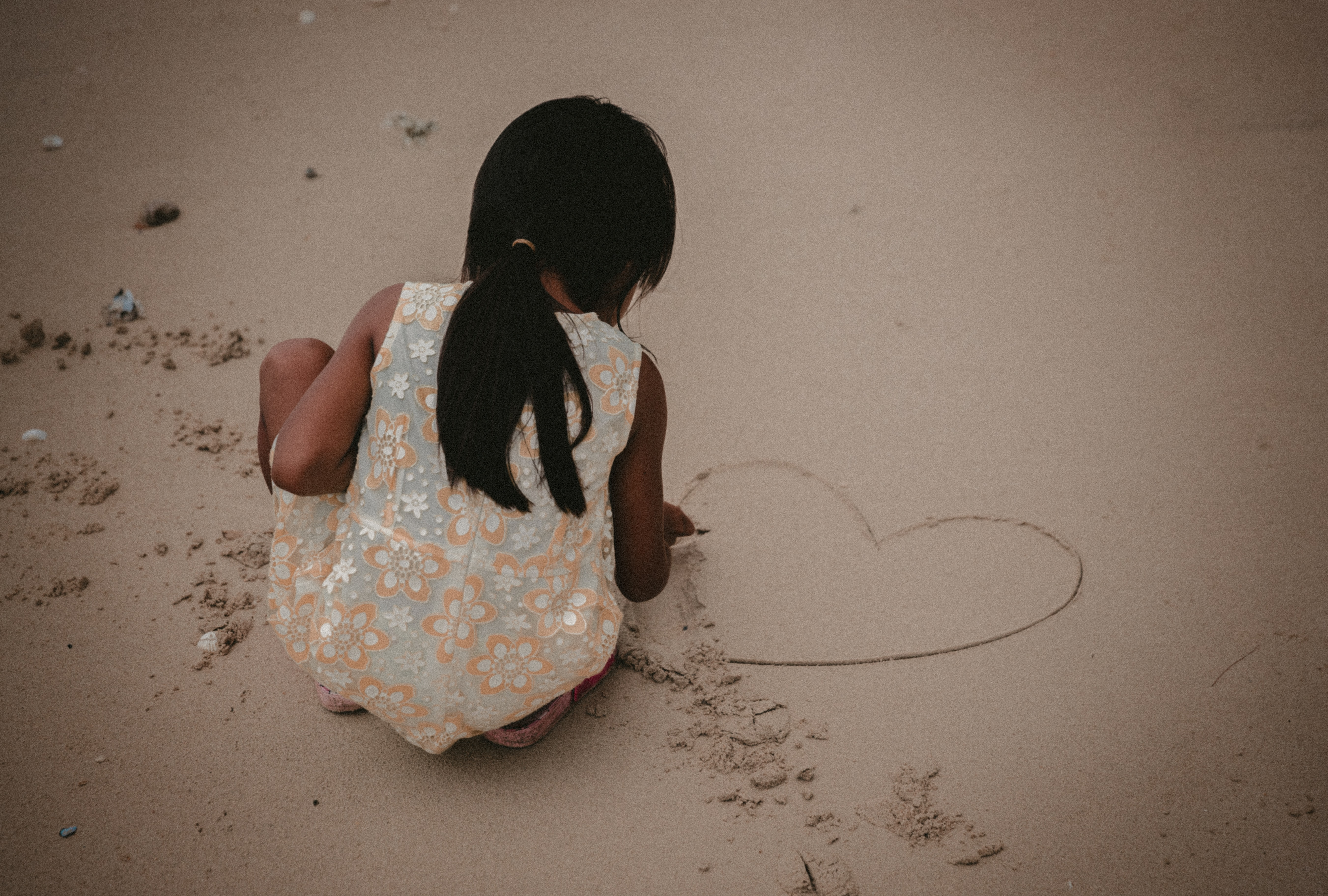 Child playing on the beach and drawing a heart in the sand