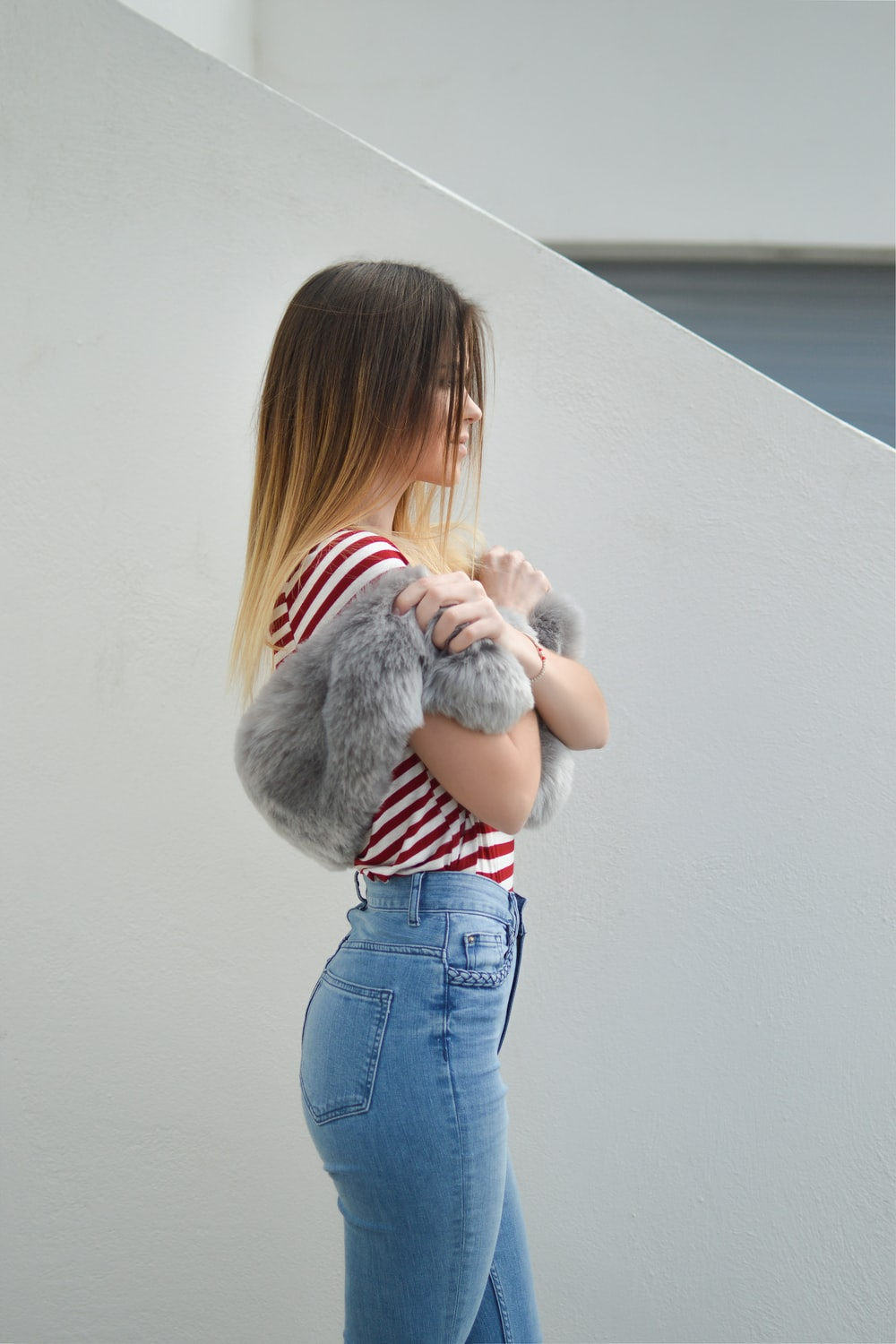 woman with pink fur scarf near wall