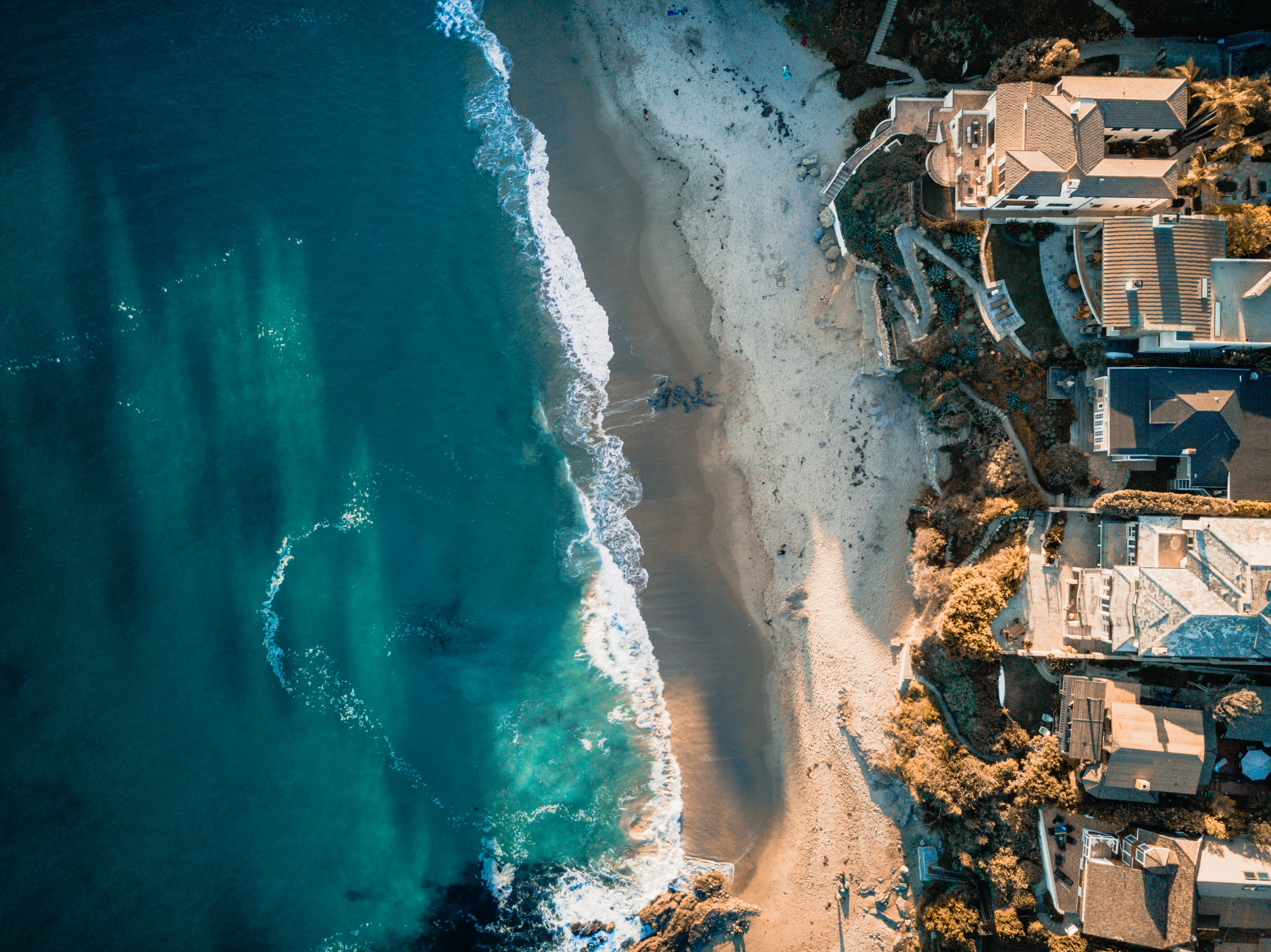 Drone aerial view of the ocean, sand beach, and houses on the Laguna Beach