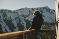 man sitting on balcony overlooking snow capped mountain