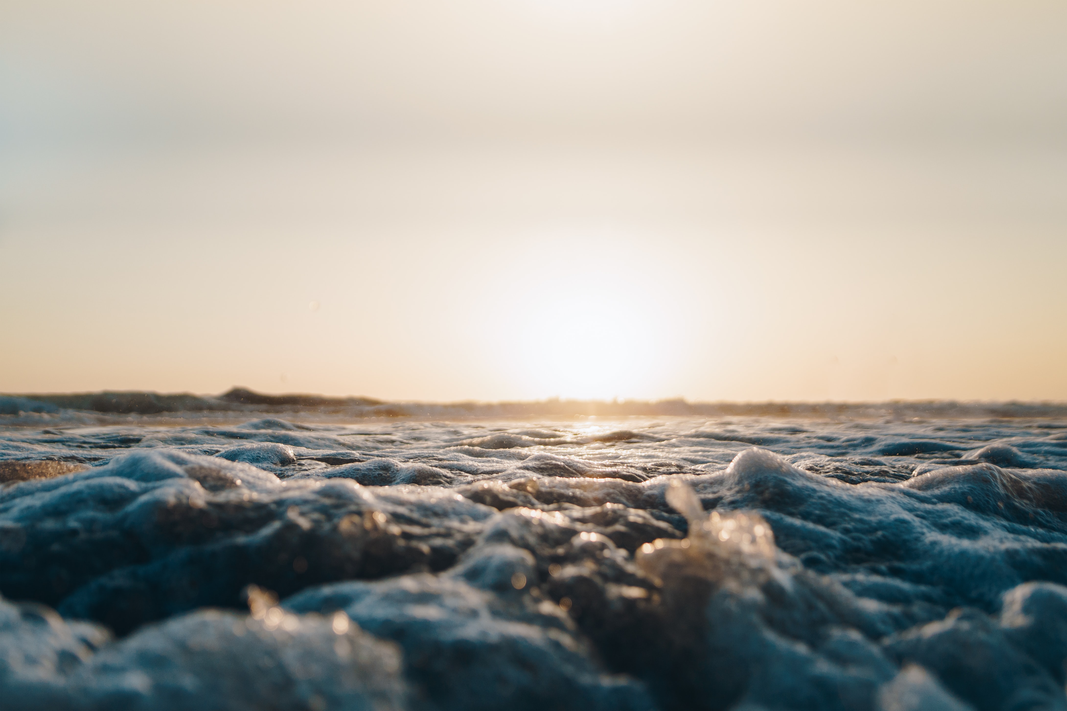 Sun setting in the distance viewed from the foamy ocean at Moonlight State