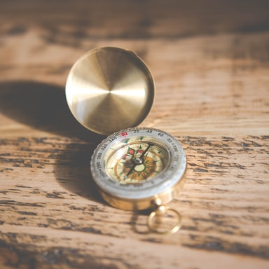 shallow focus photography of compass on brown table