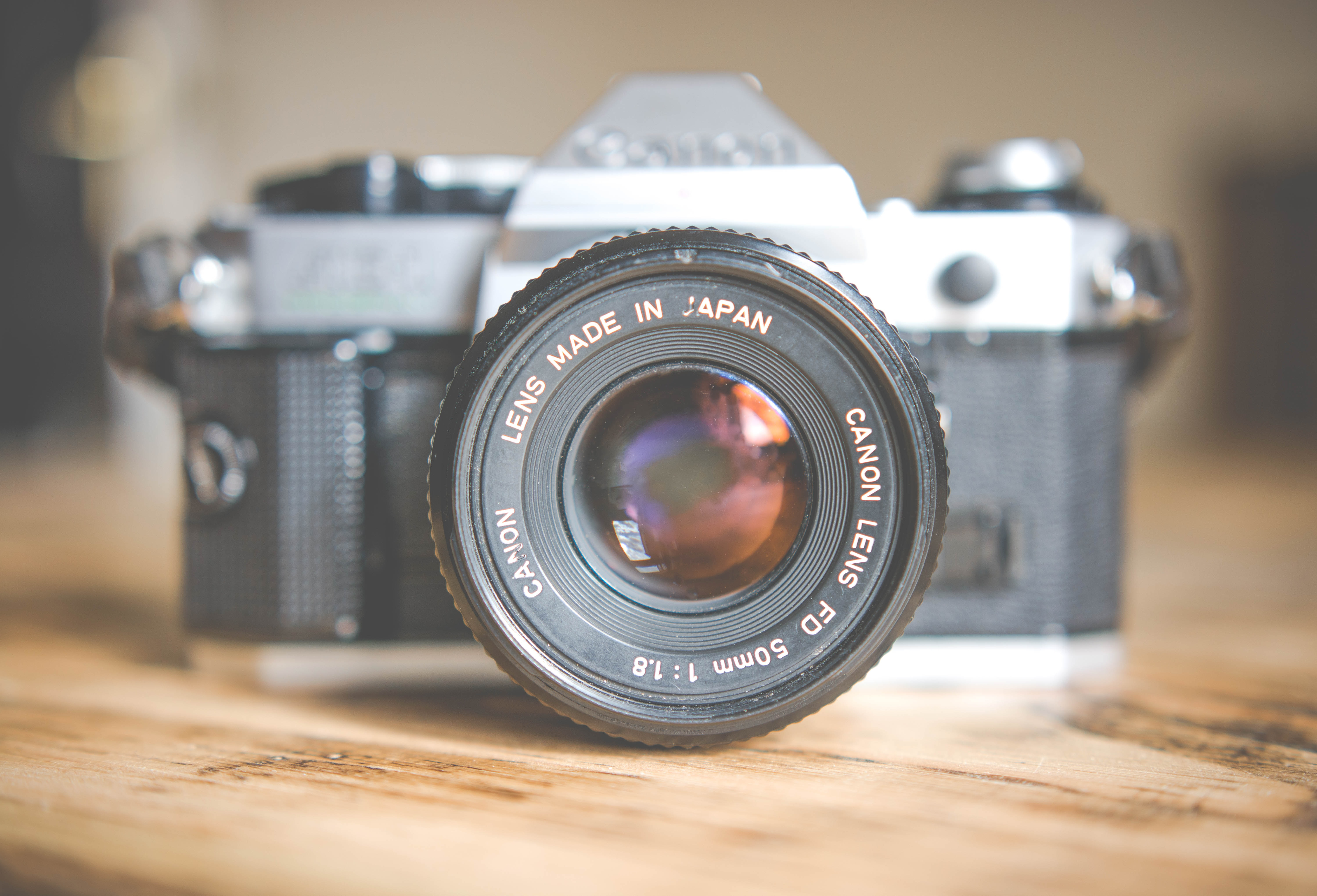 Canon lens on a vintage canon camera on a wooden surface