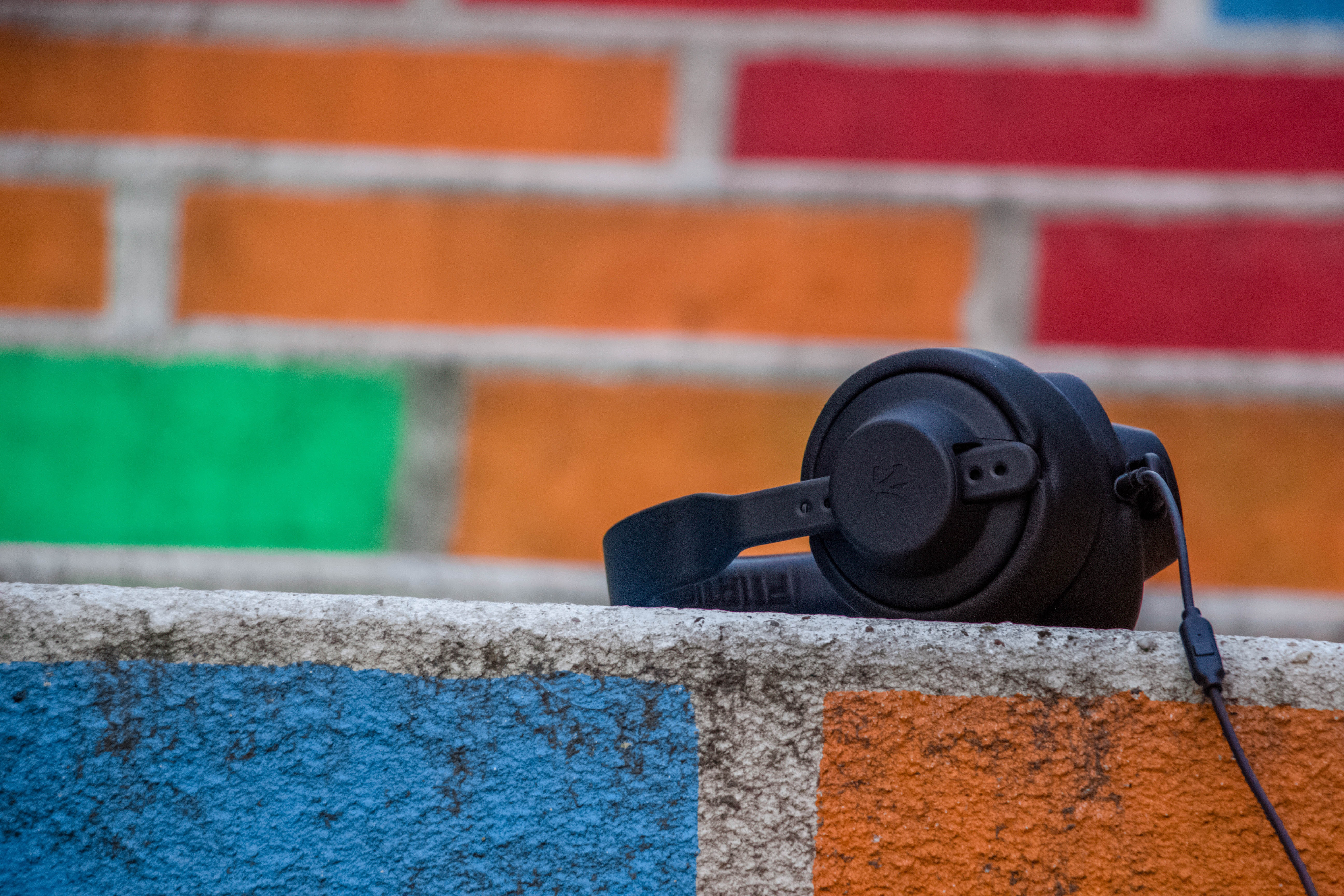 Black headphones on colorful wall with painted bricks