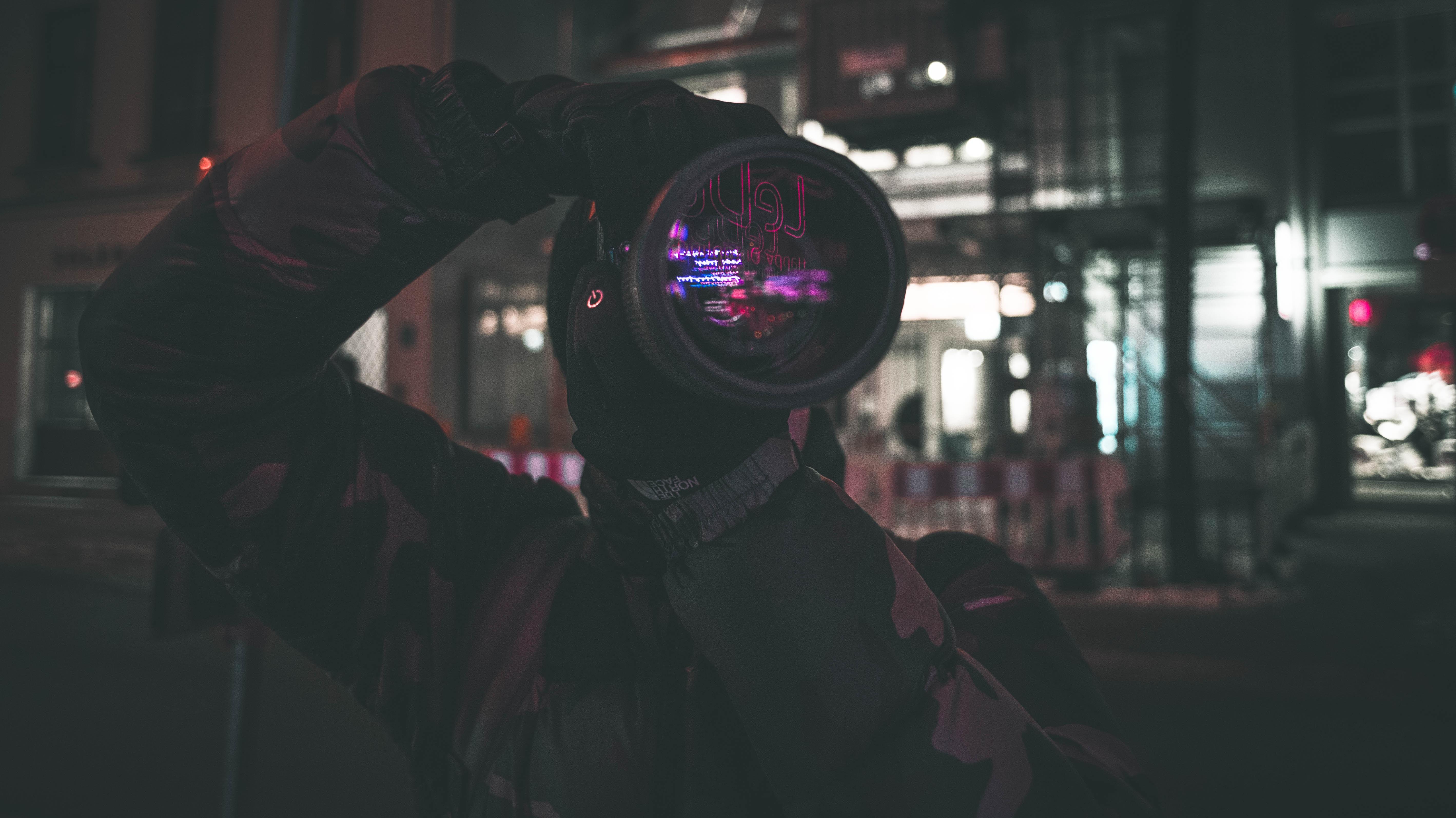 man holding camera standing near building