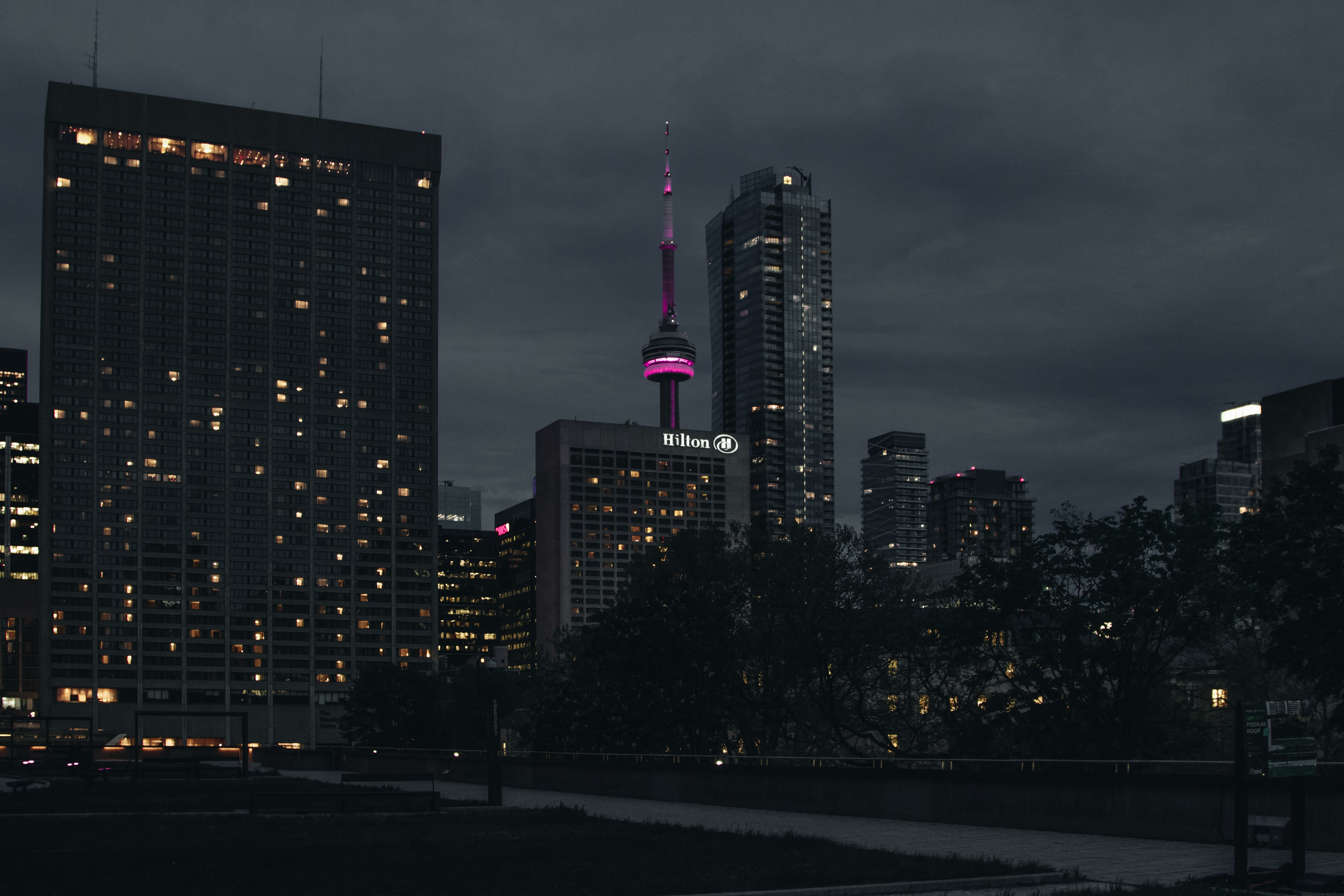 A dim cityscape of Toronto with the CN tower lit up in purple