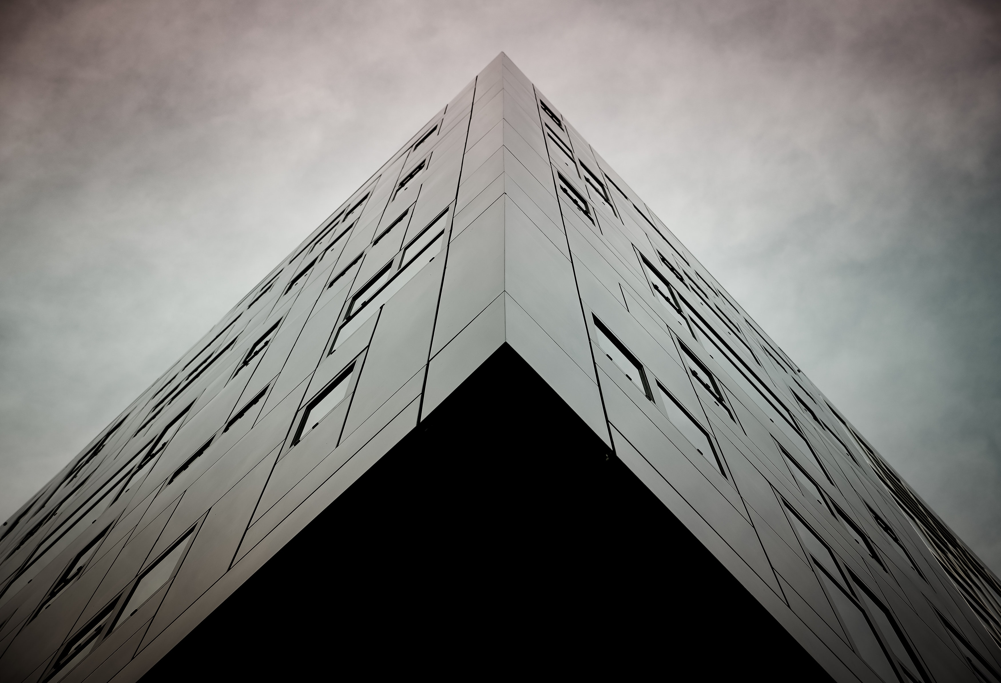 Corner of a black modern building under a gray sky