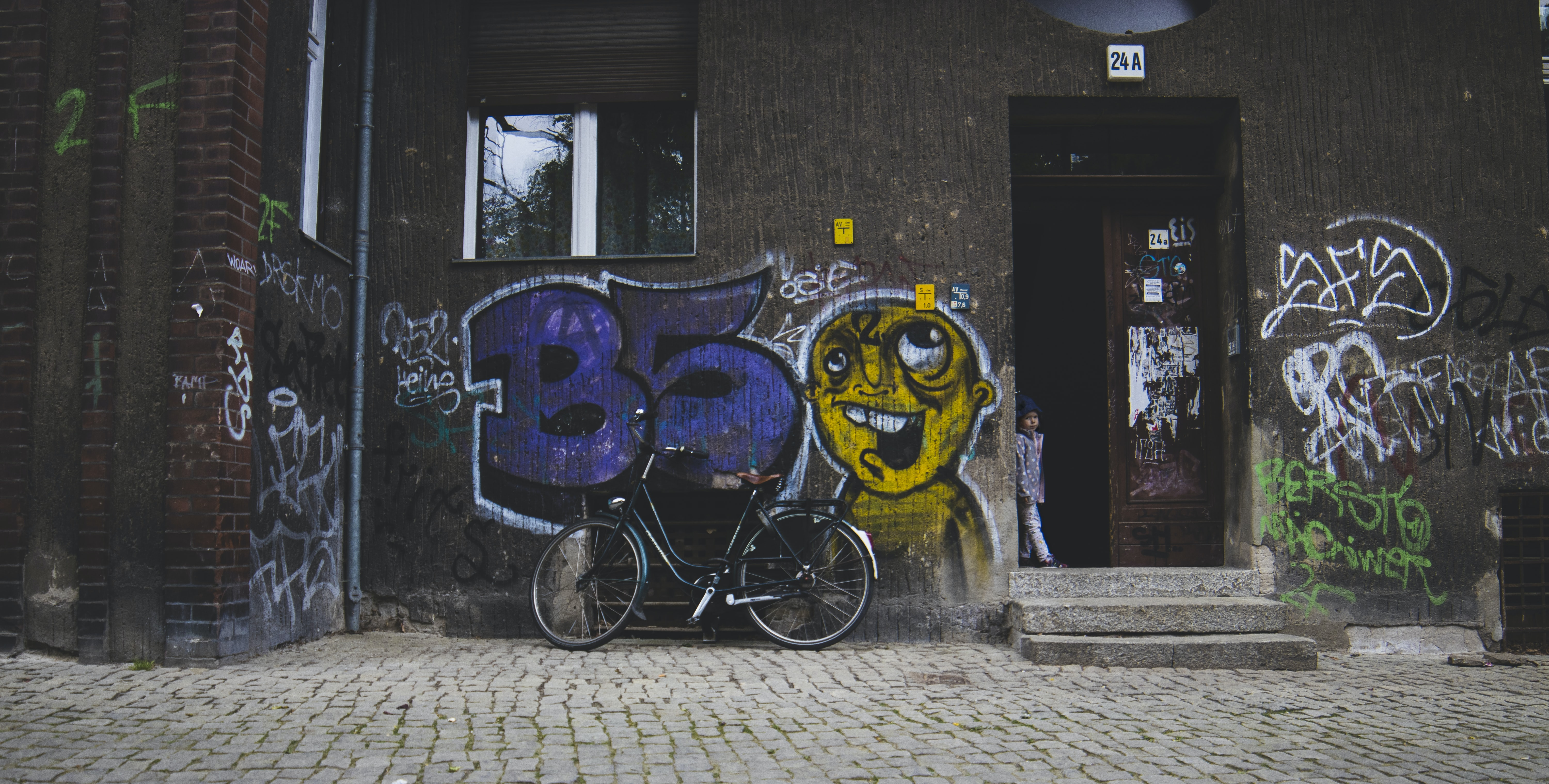black bicycle parked near brown wall