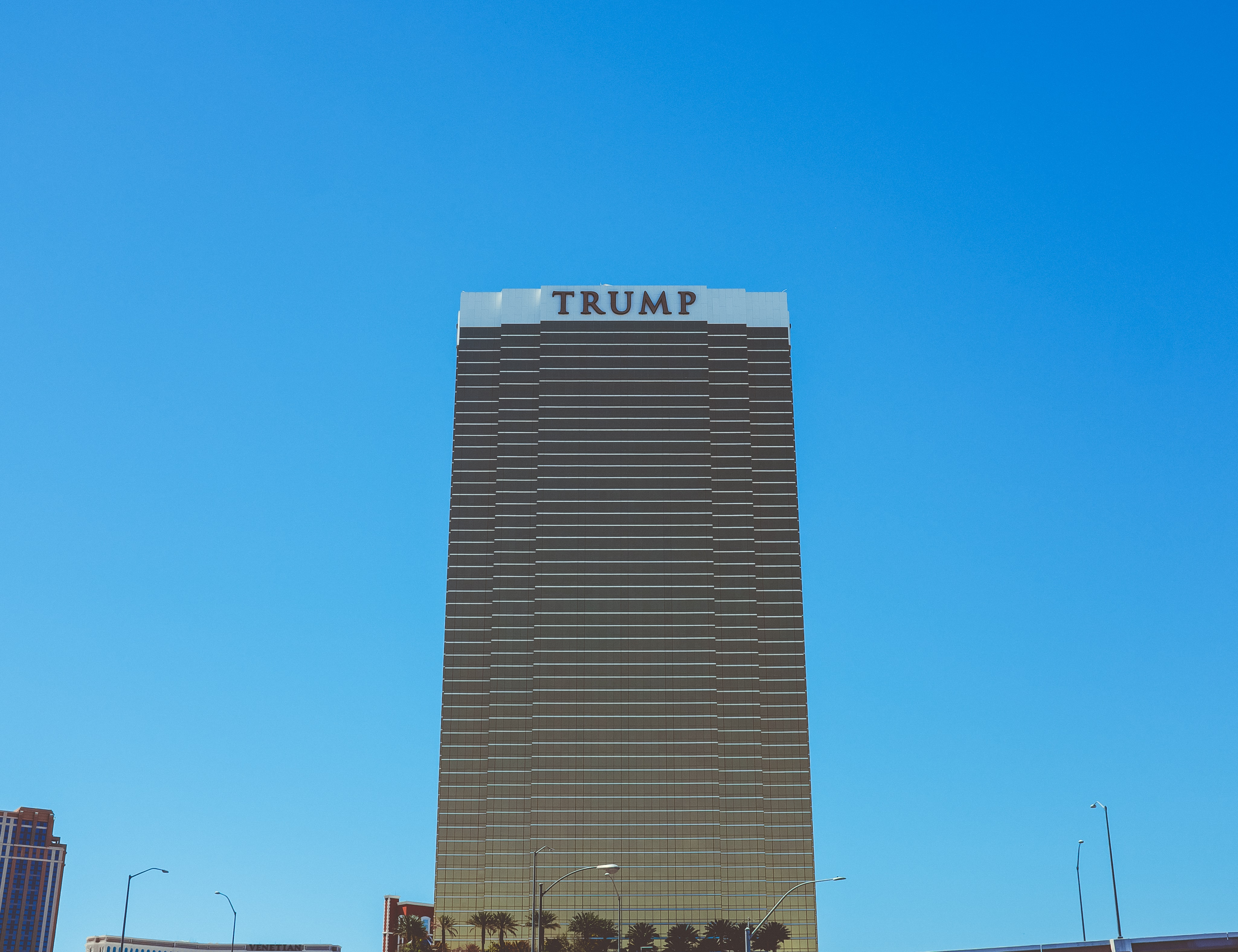 Faraway shot of Trump International Hotel Las Vegas with palm trees near the base
