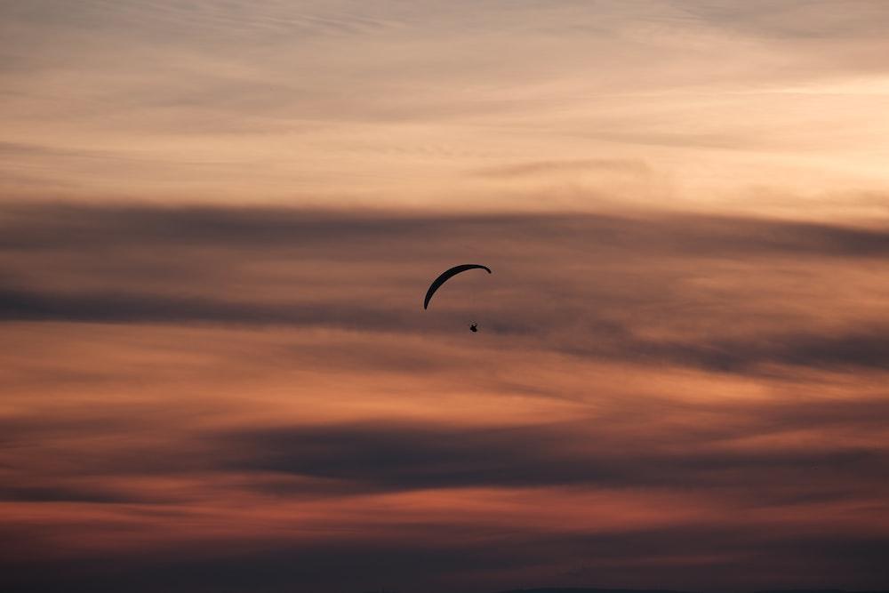 person gliding parachute in sky