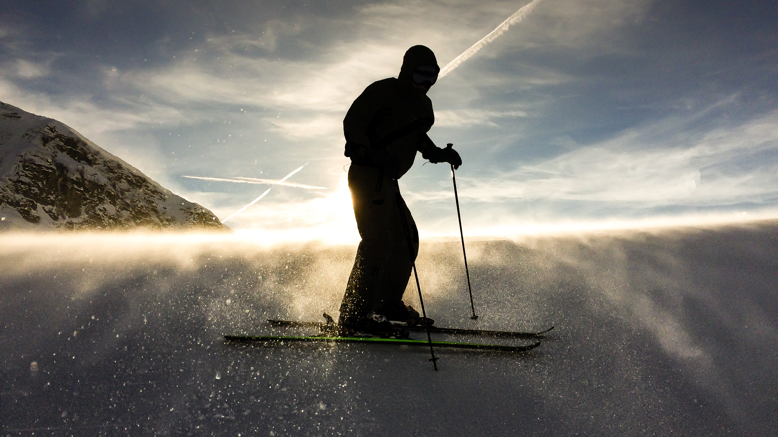 A man skiing through snow while the sun breaks free from clouds
