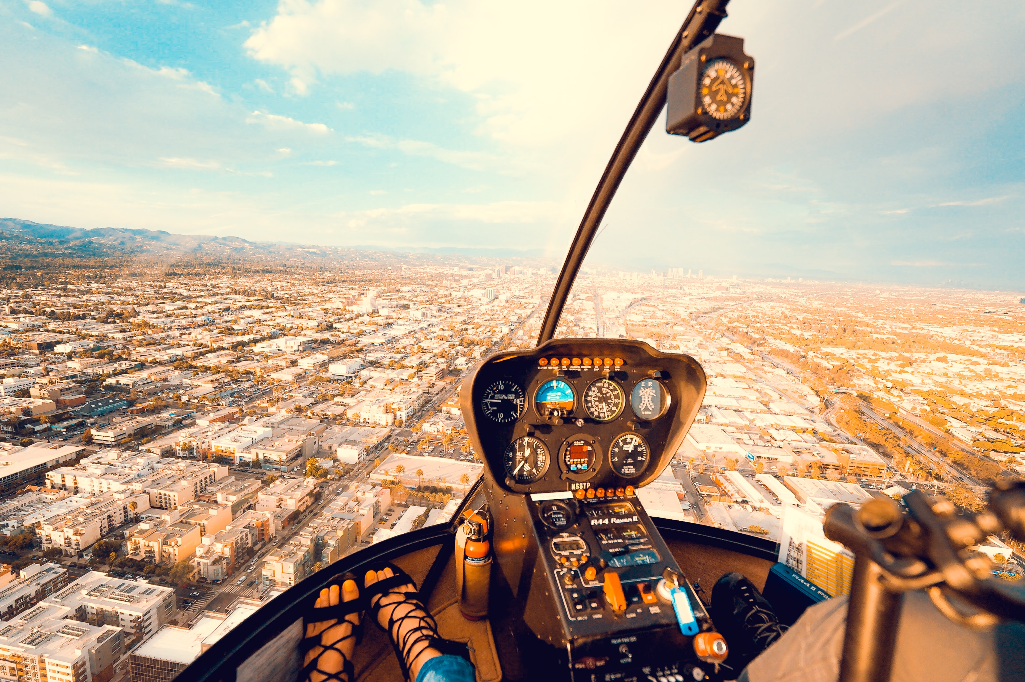 Inside the cockpit of a helicopter flying above a busy city downtown