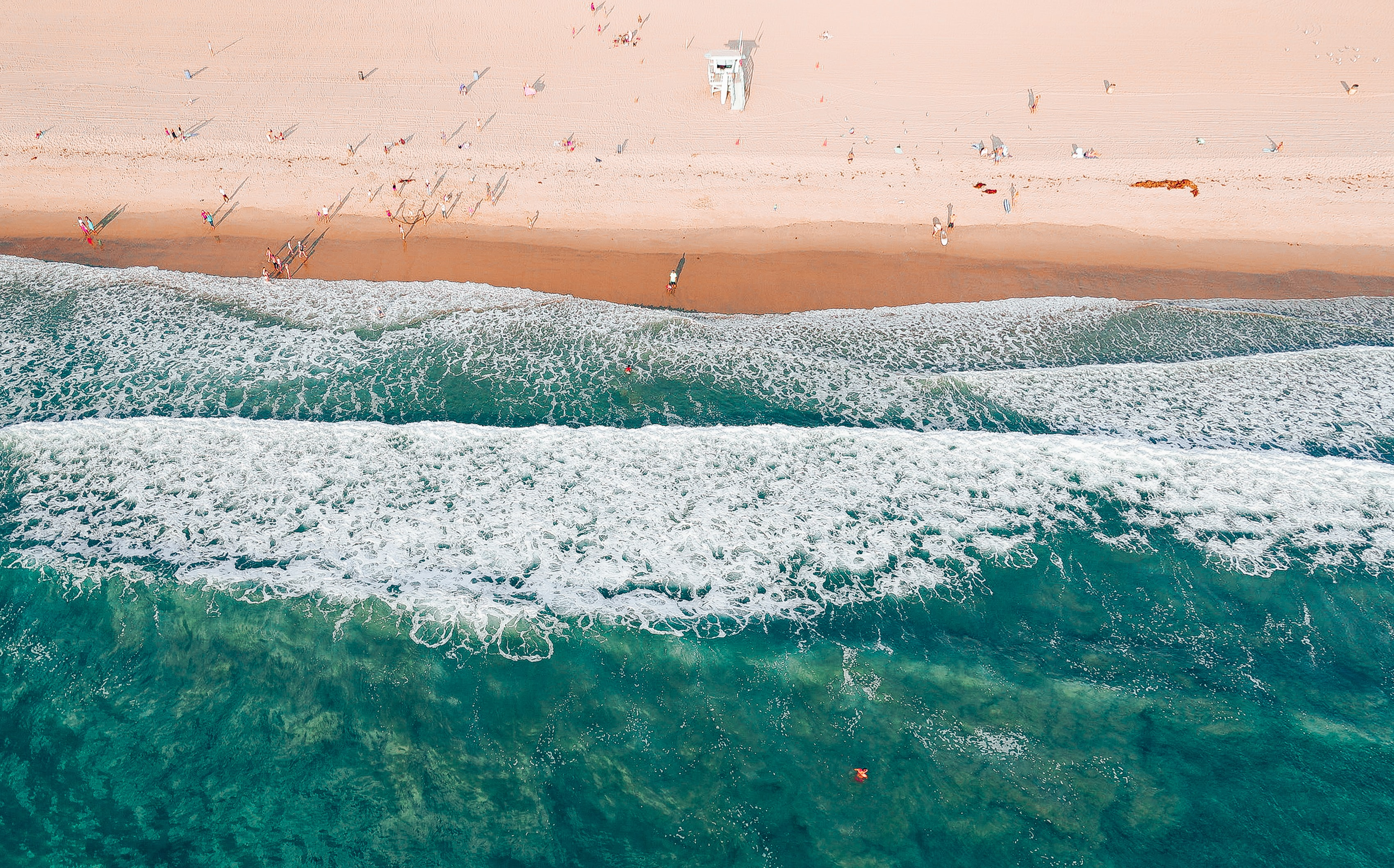 A drone view of people hanging out at the beach, swimming and tanning