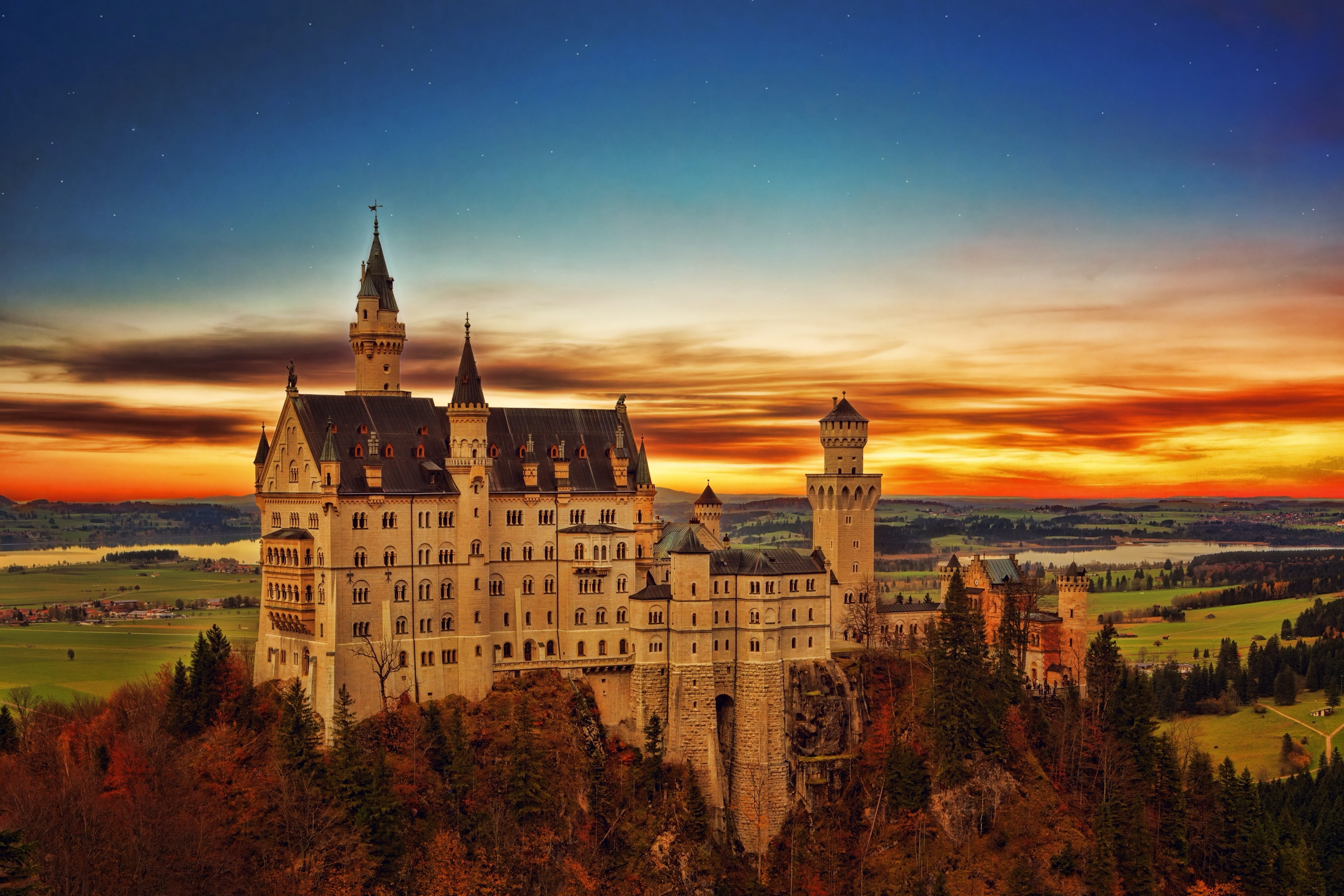 Drone view of Neuschwanstein Castle and country landscape with orange and blue sunrise-or-sunset horizon