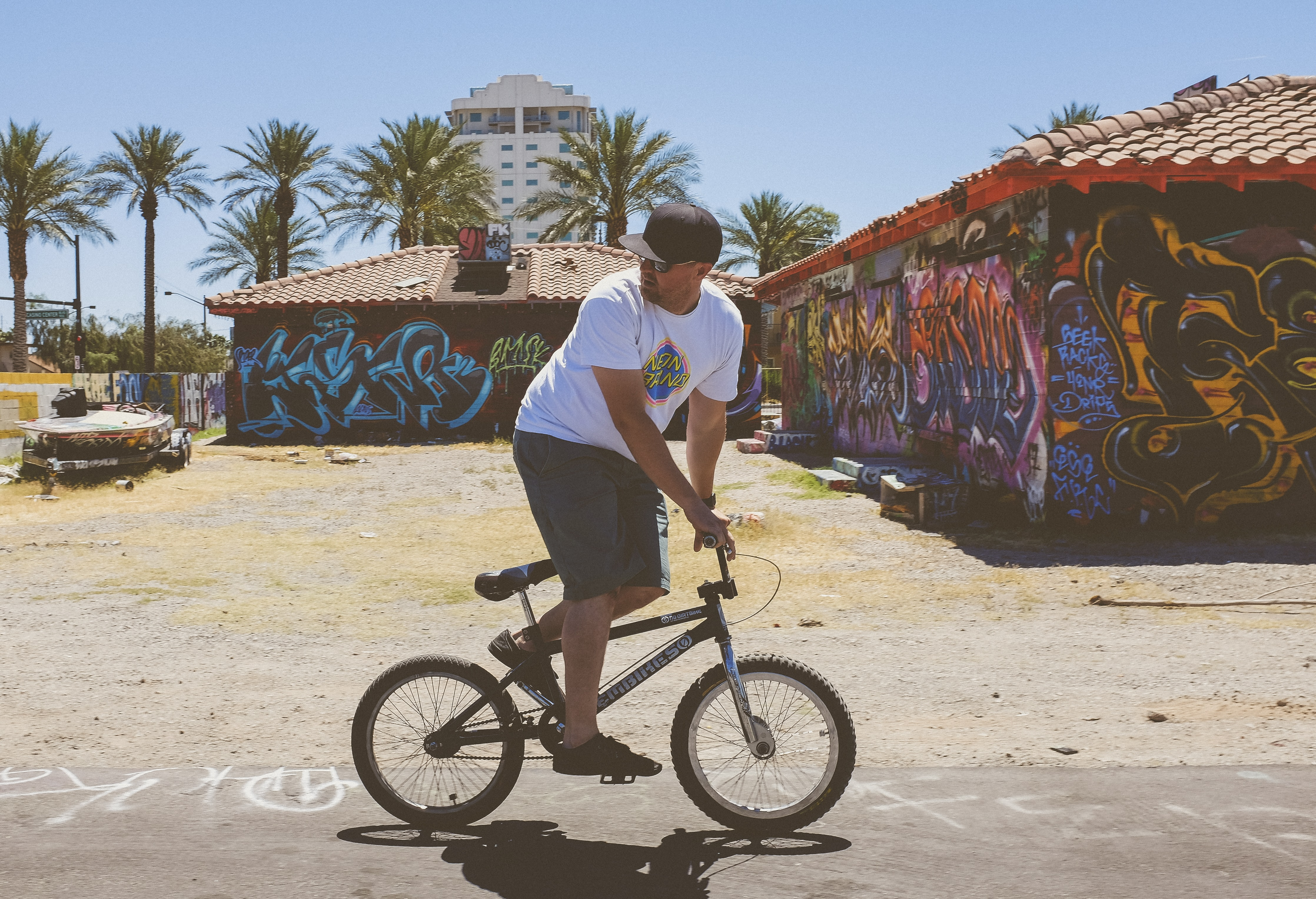 Man riding BMX on dusty road near graffiti covered buildings near palm trees in Arts District
