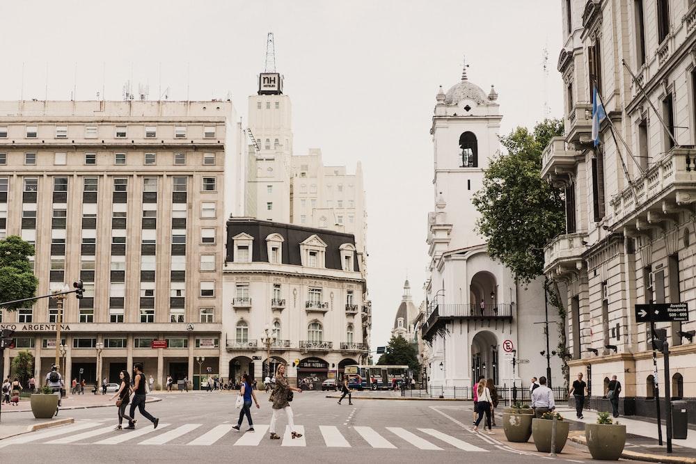 woman crossing pedestrian lane between tall buildings