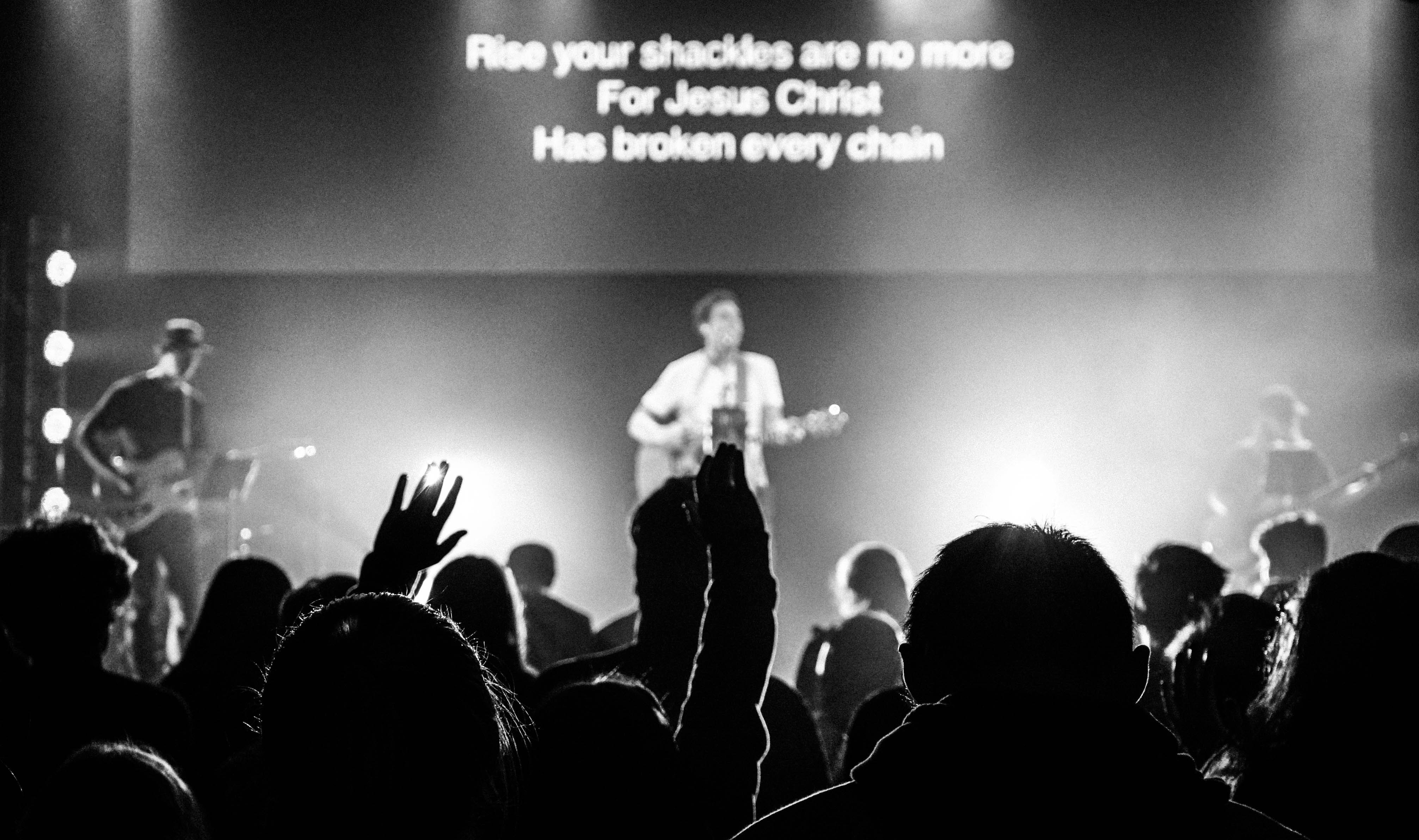 Silhouettes of an audience holding their arms up during a Christian rock concert