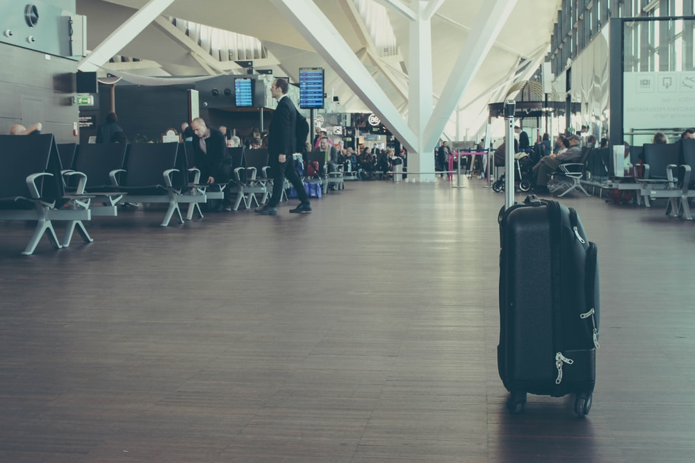 unattended black luggage inside airport