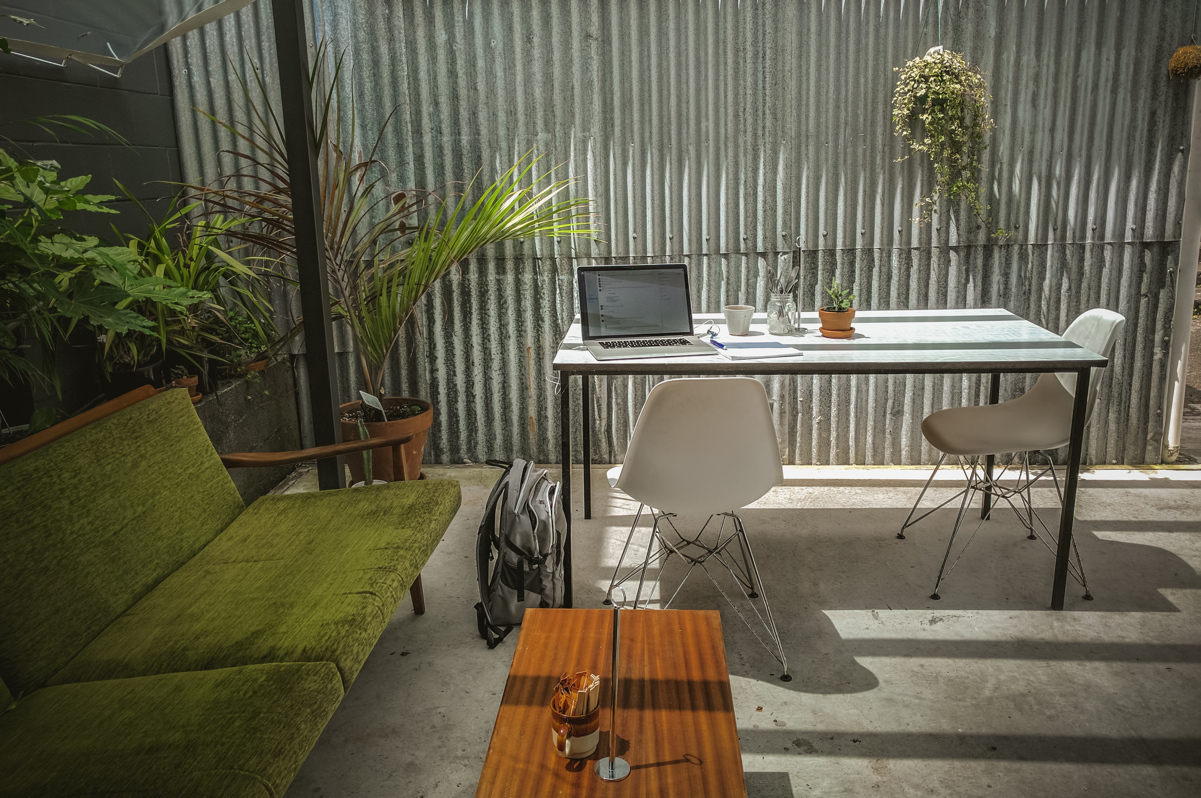 Outside deskspace against a corrugated metal wall with plants and sunlight