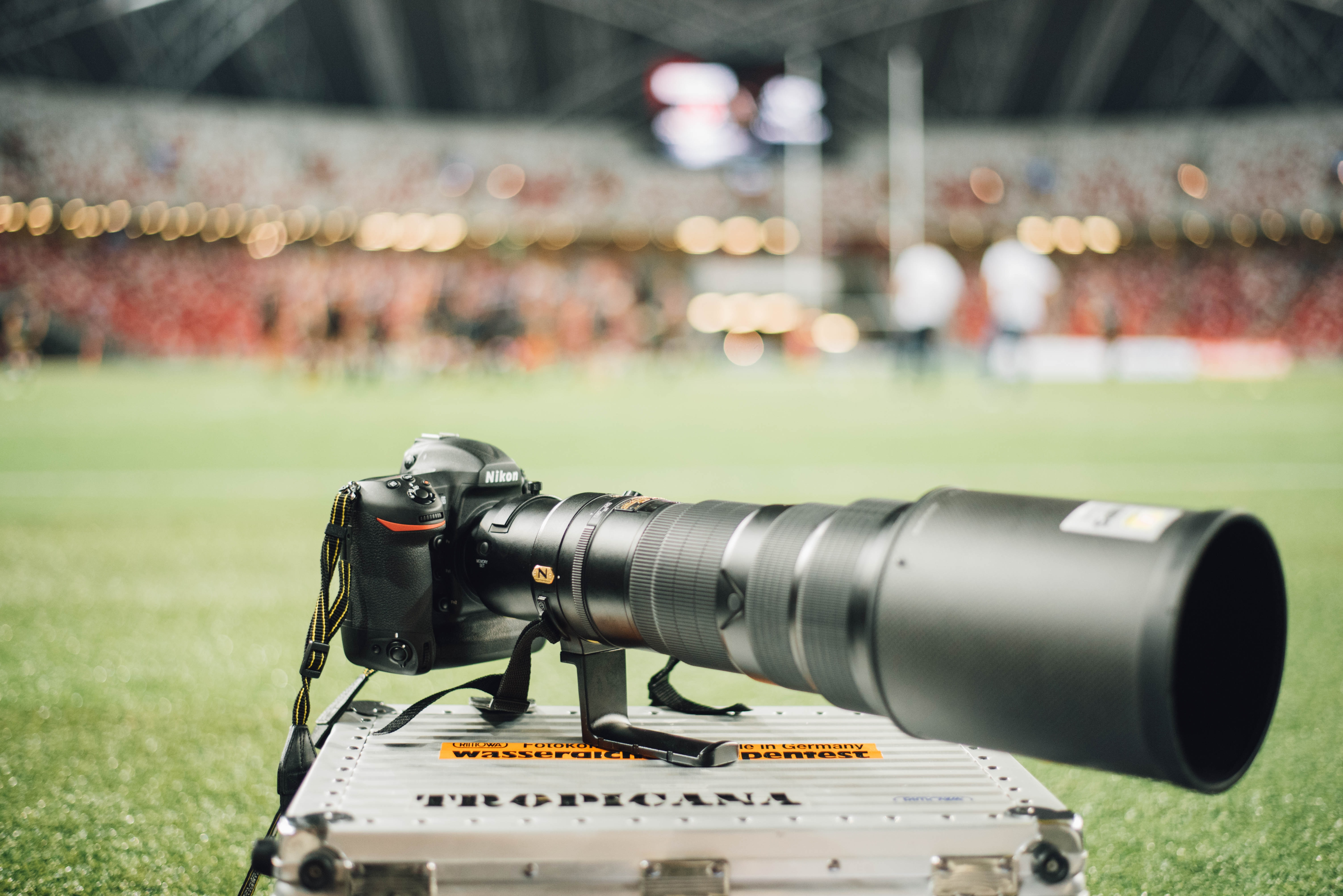 A long-lens camera on a steel crate in a soccer field