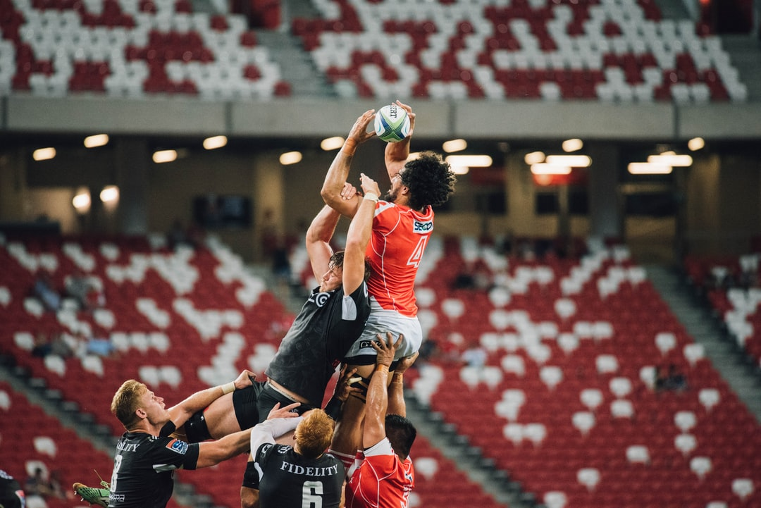 A shot of two rugby players jumping high for a ball as other players make a rush