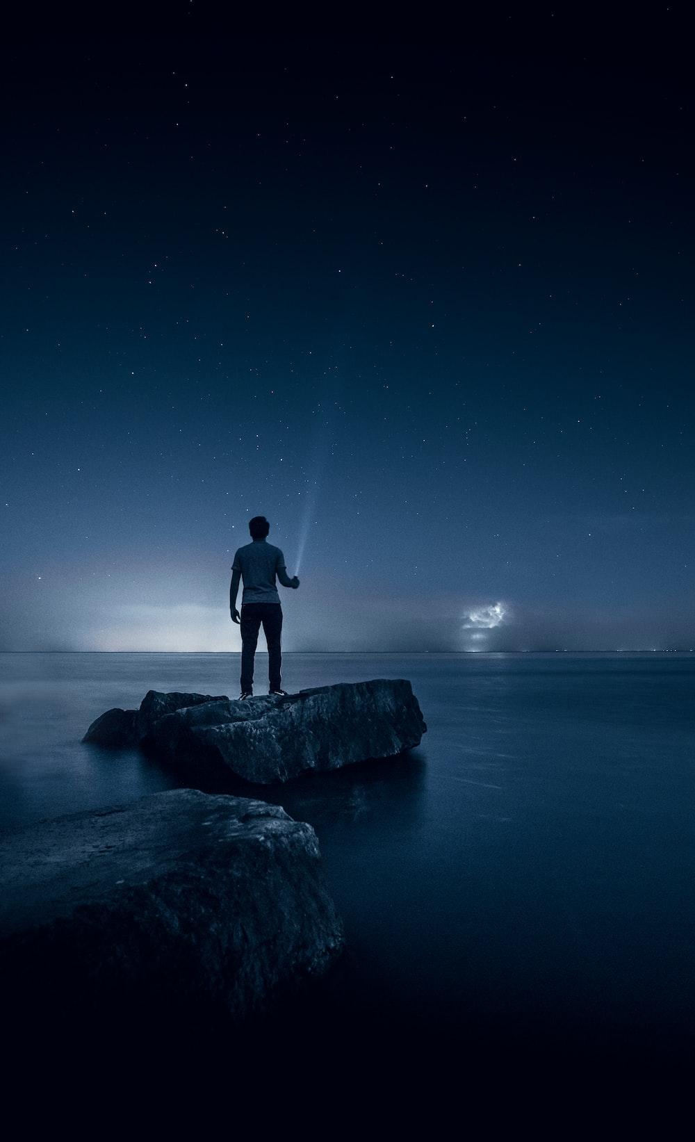 man holding flashlight standing on rock