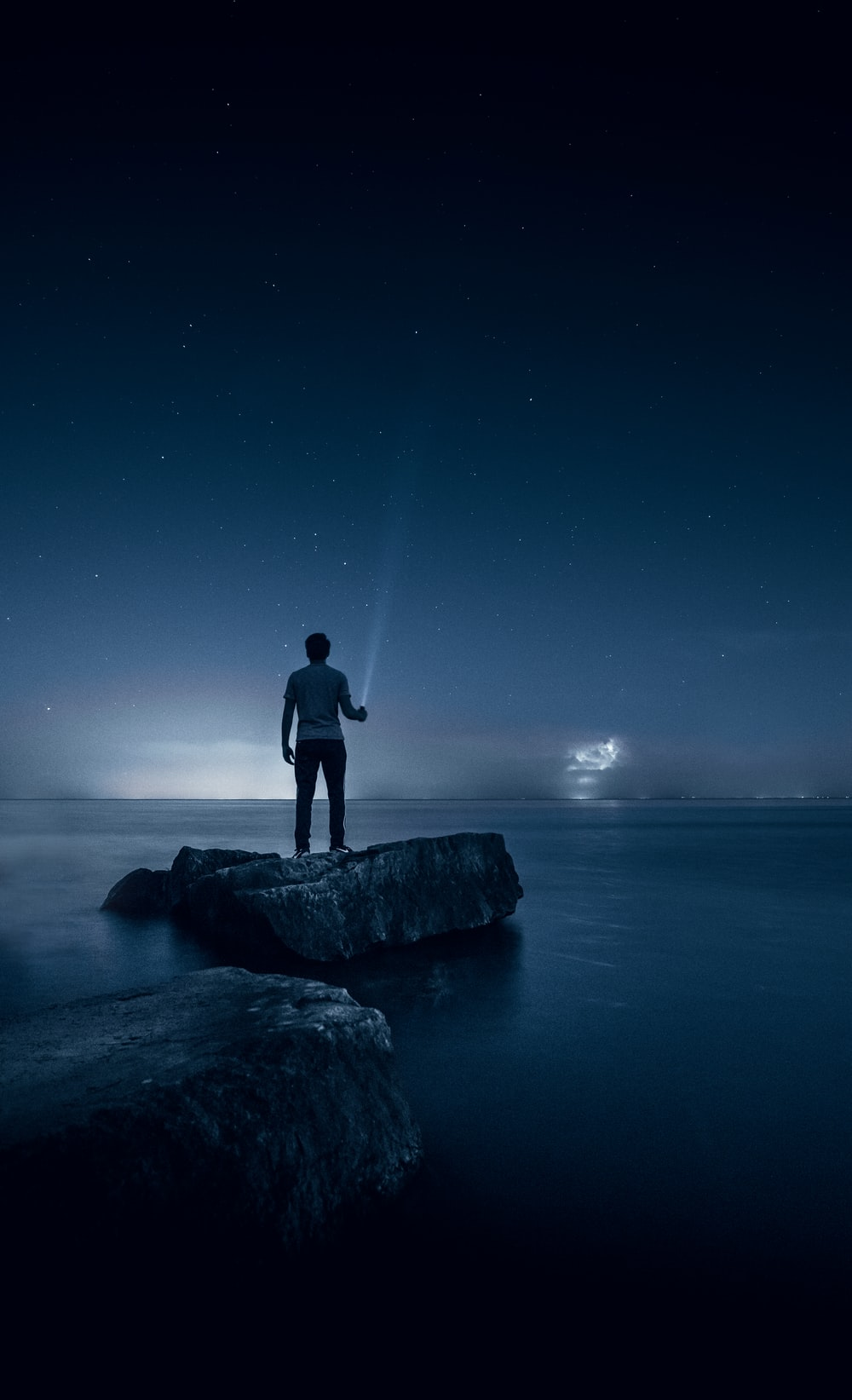 man holding flashlight standing on rock