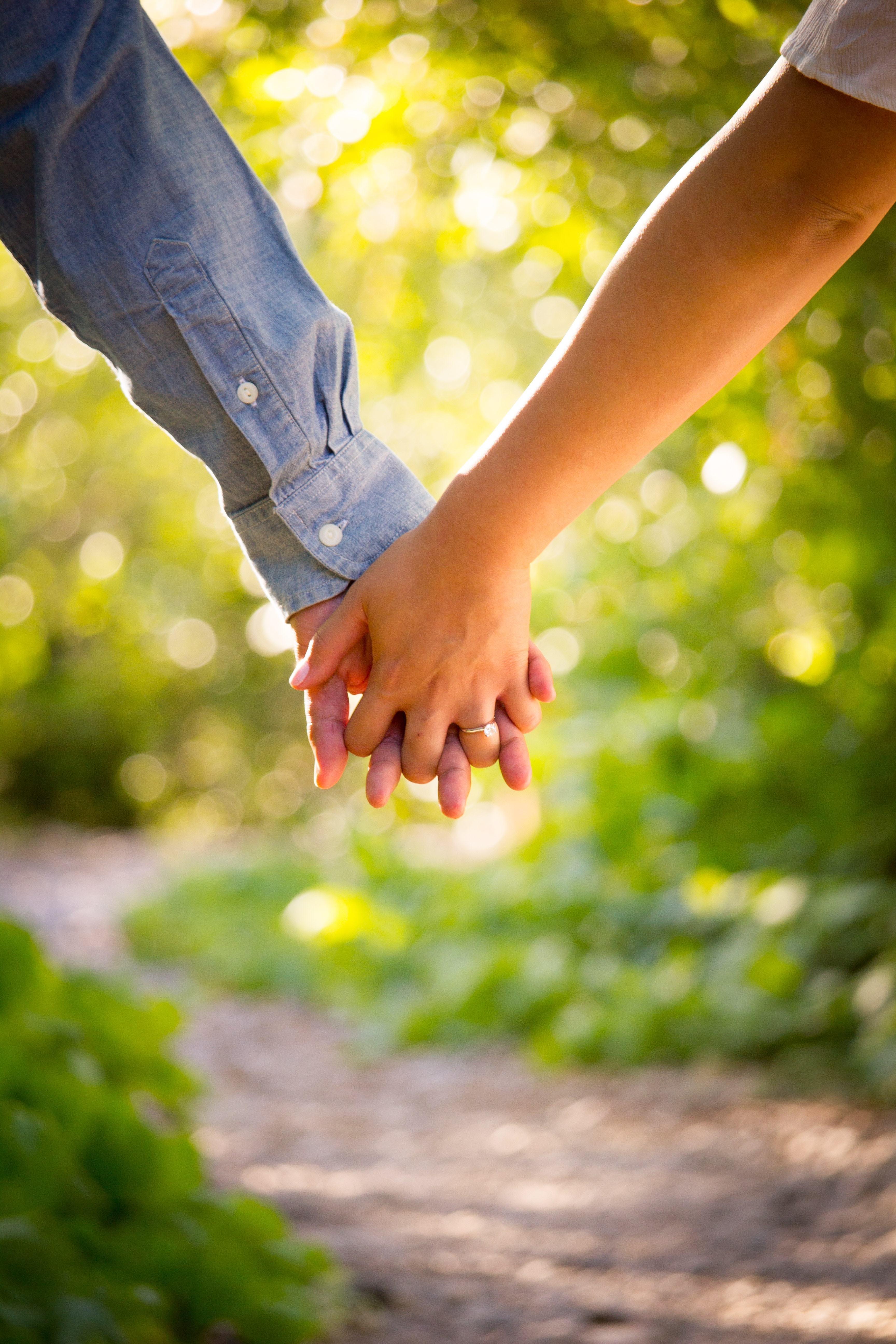 Close-up of couple's interlaced hands on a trail in afternoon