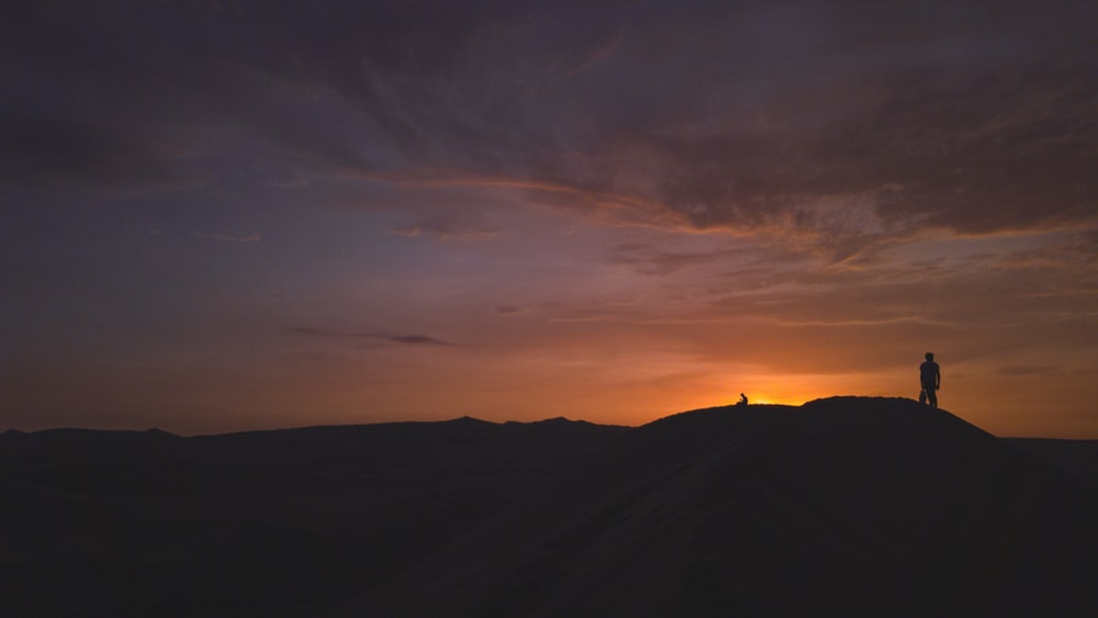 silhouette of person standing on hill during golden hour