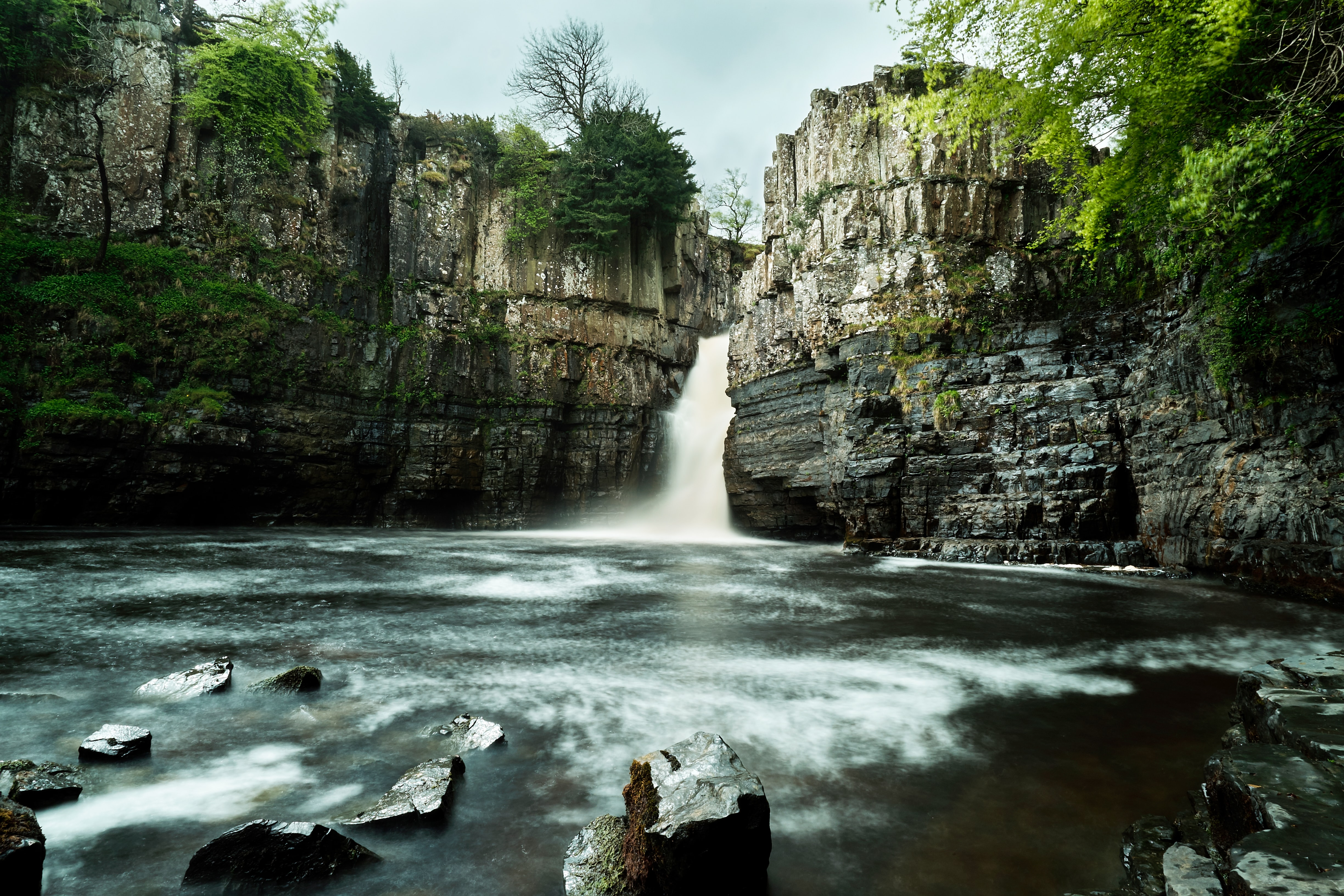 A view of the High Force Waterfall in England, flowing through a canyon and into a gorge