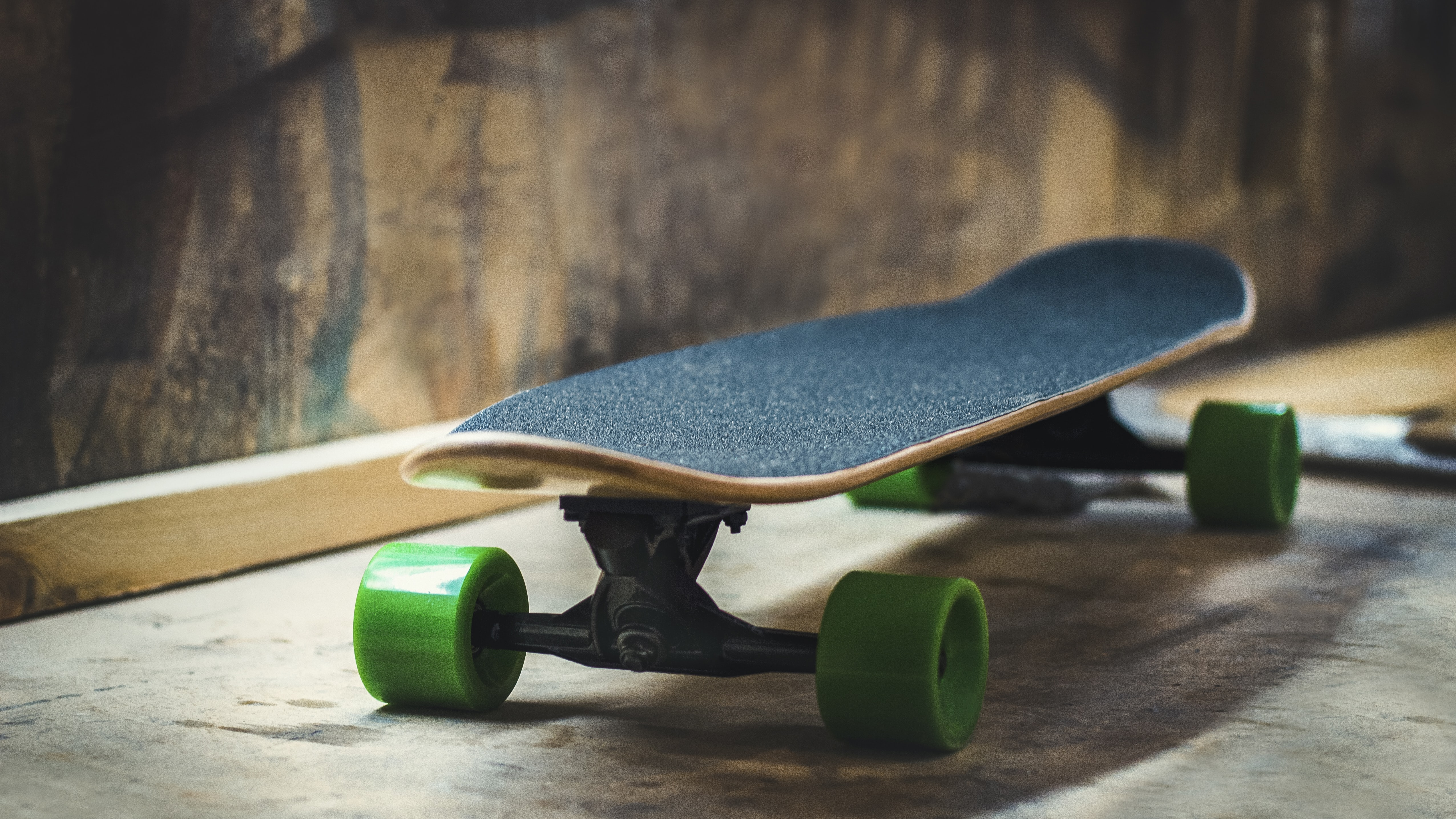 Blue skateboard with green wheels near a wooden wall